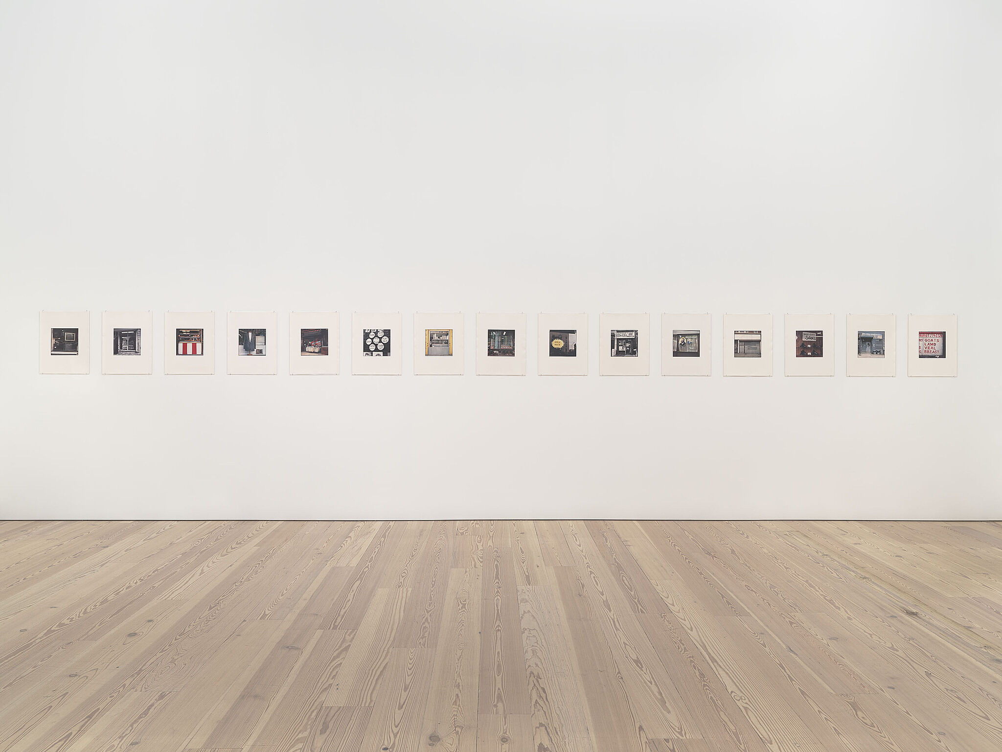 A photo of the Whitney galleries with a row of photos on the wall.