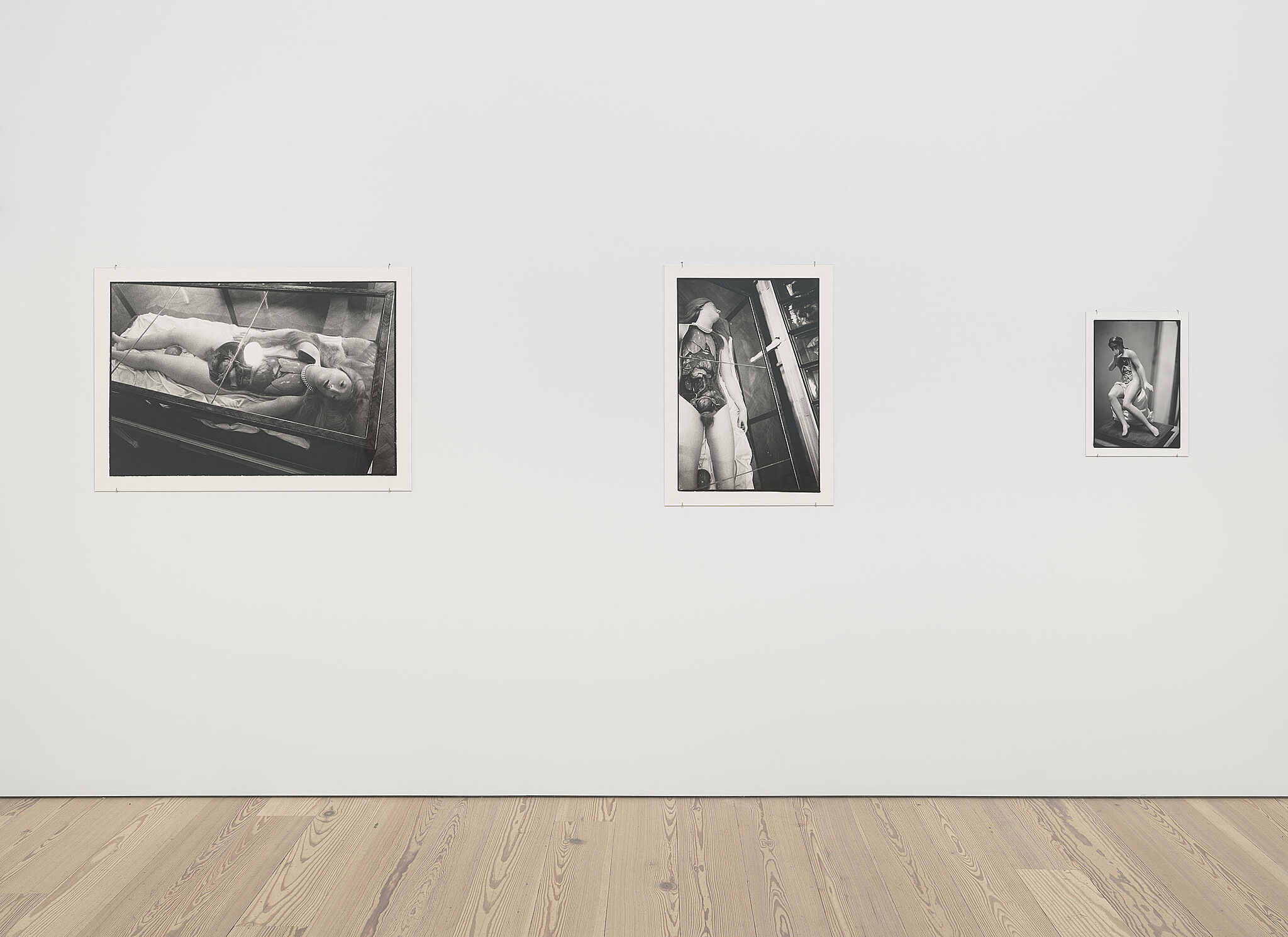 Three black and white photographs on a gallery wall.