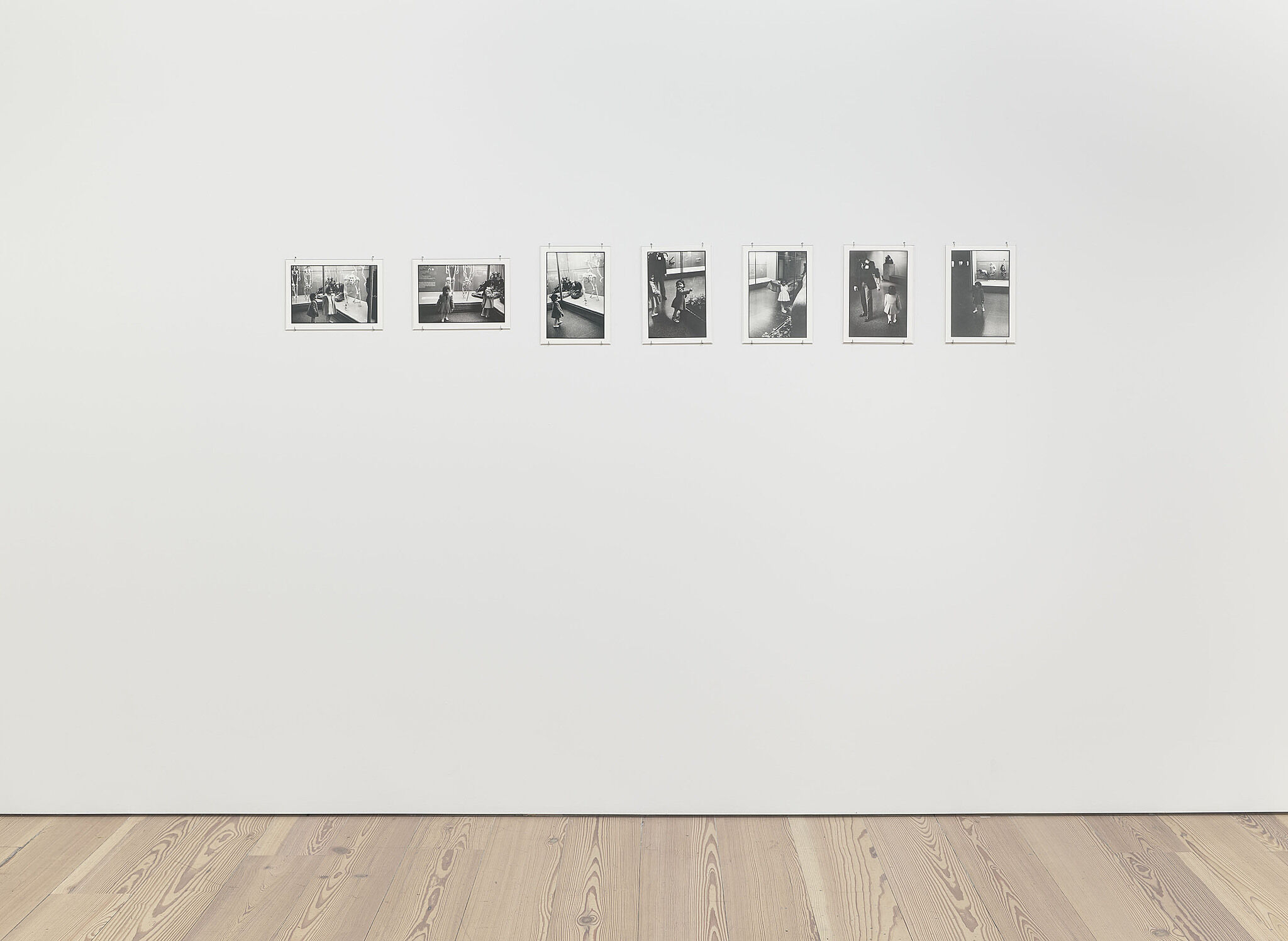 Seven black and white photos on a gallery wall.