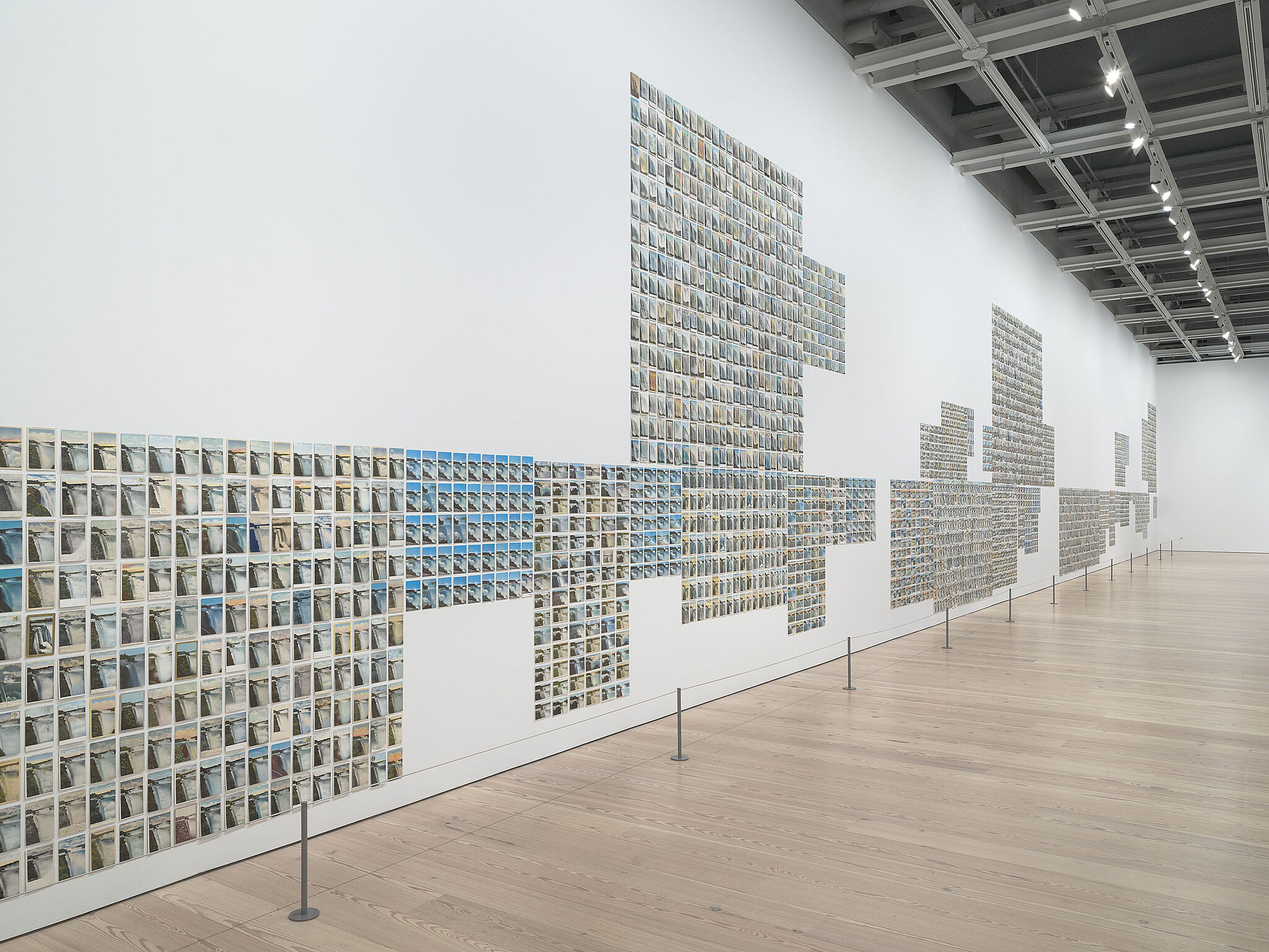 A gallery wall covered with hundreds of postcards.