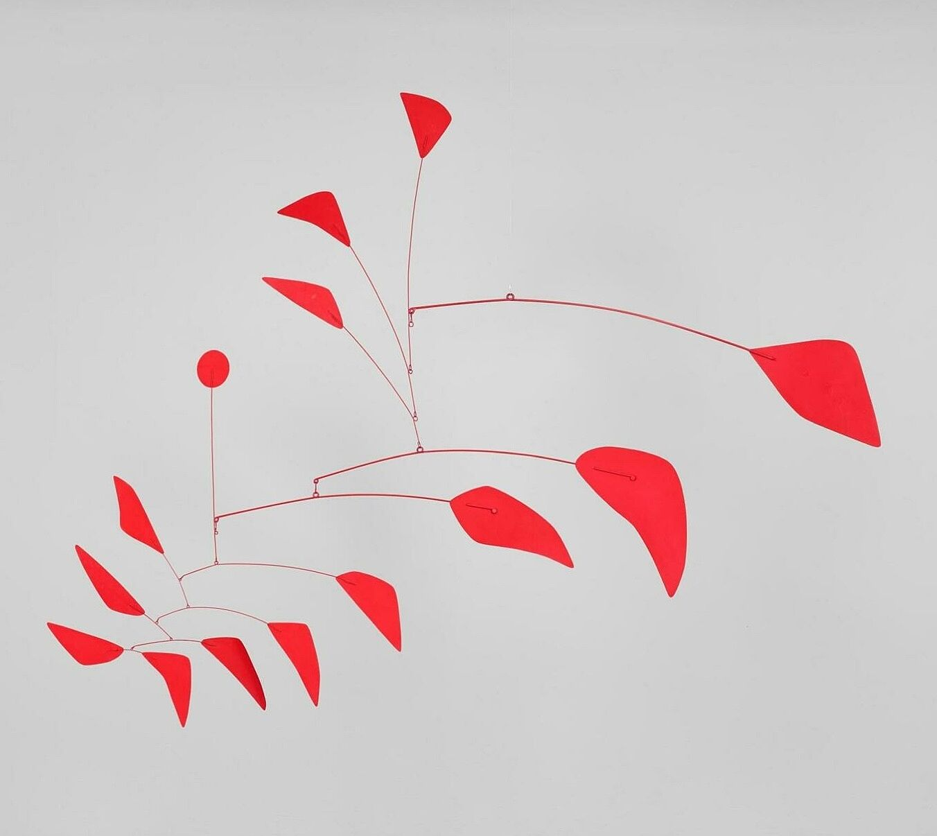 Red hanging mobile on a gray background.