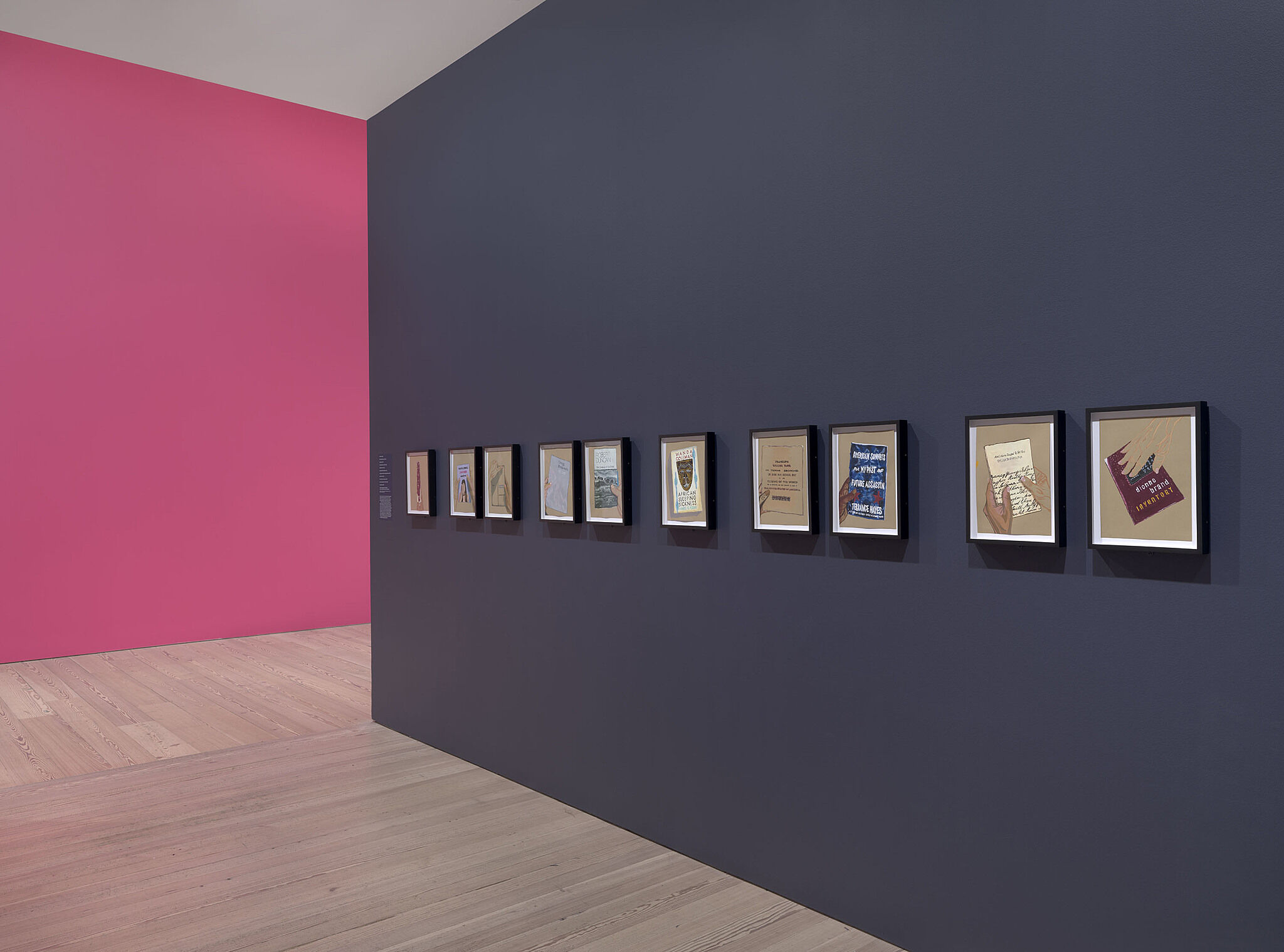 A series of small paintings on a gallery wall.