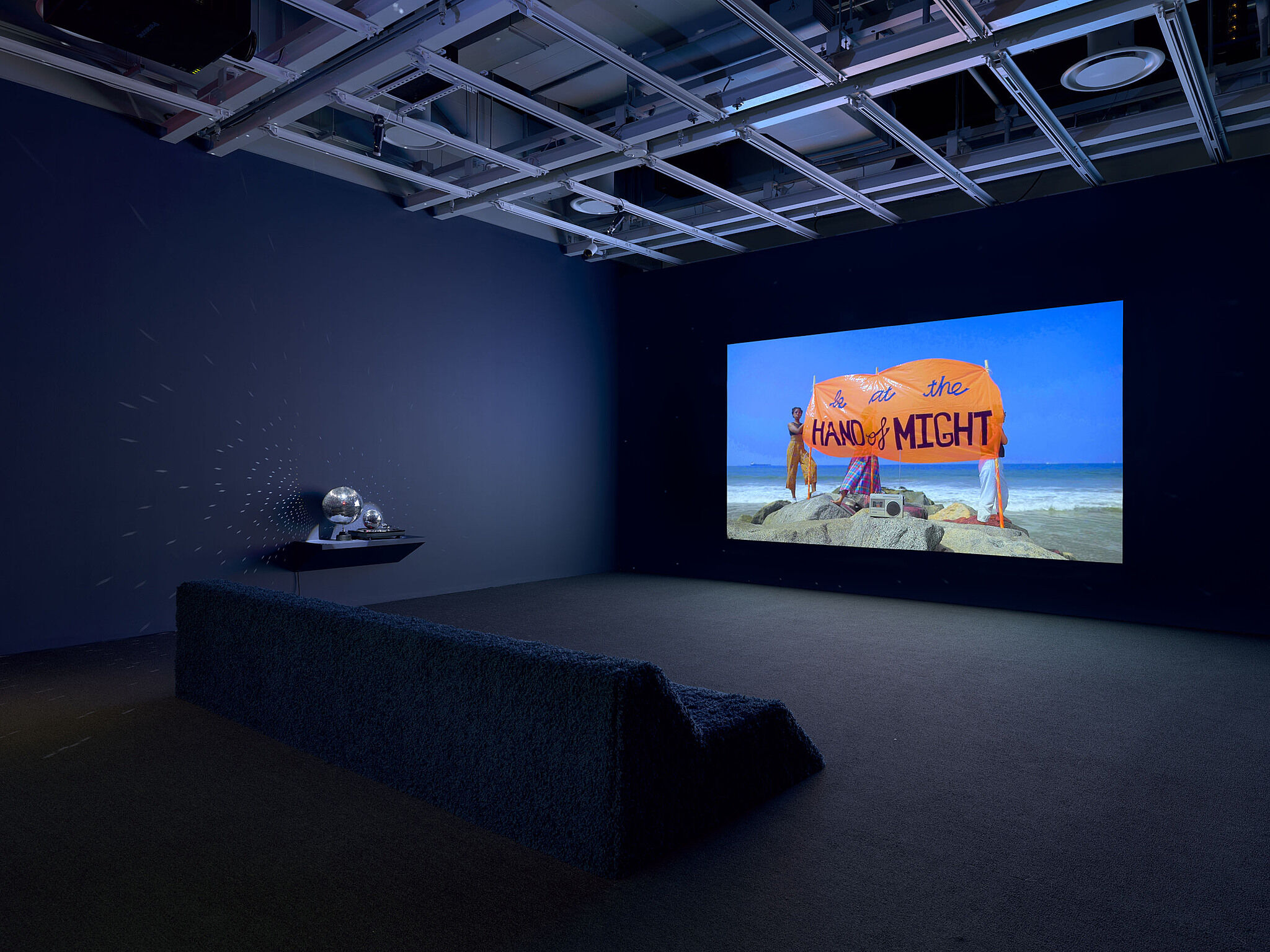 A large video screen in a dark gallery with a disco ball off to the side.