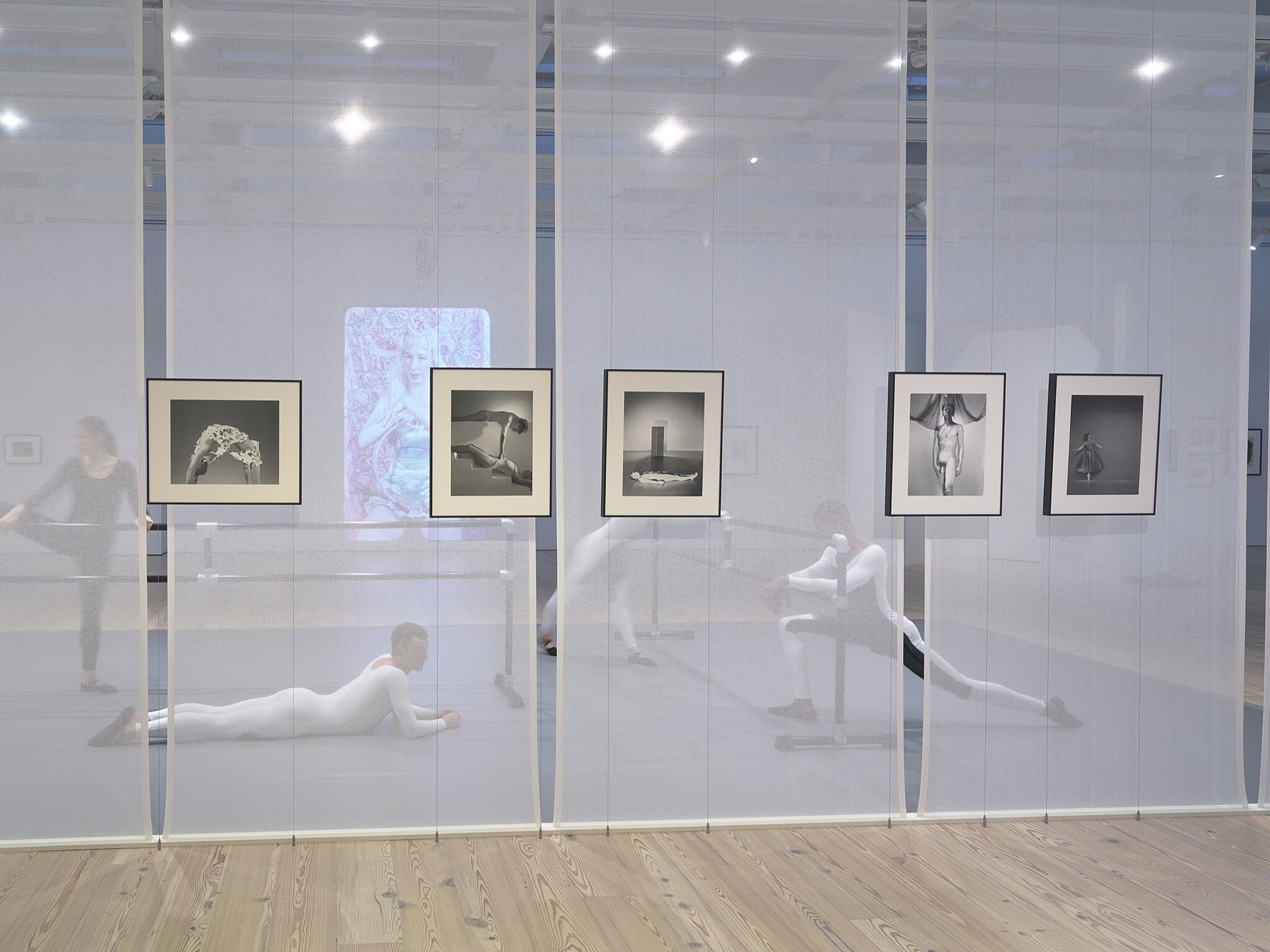A group of dancers stretching in a gallery with photos on the walls.