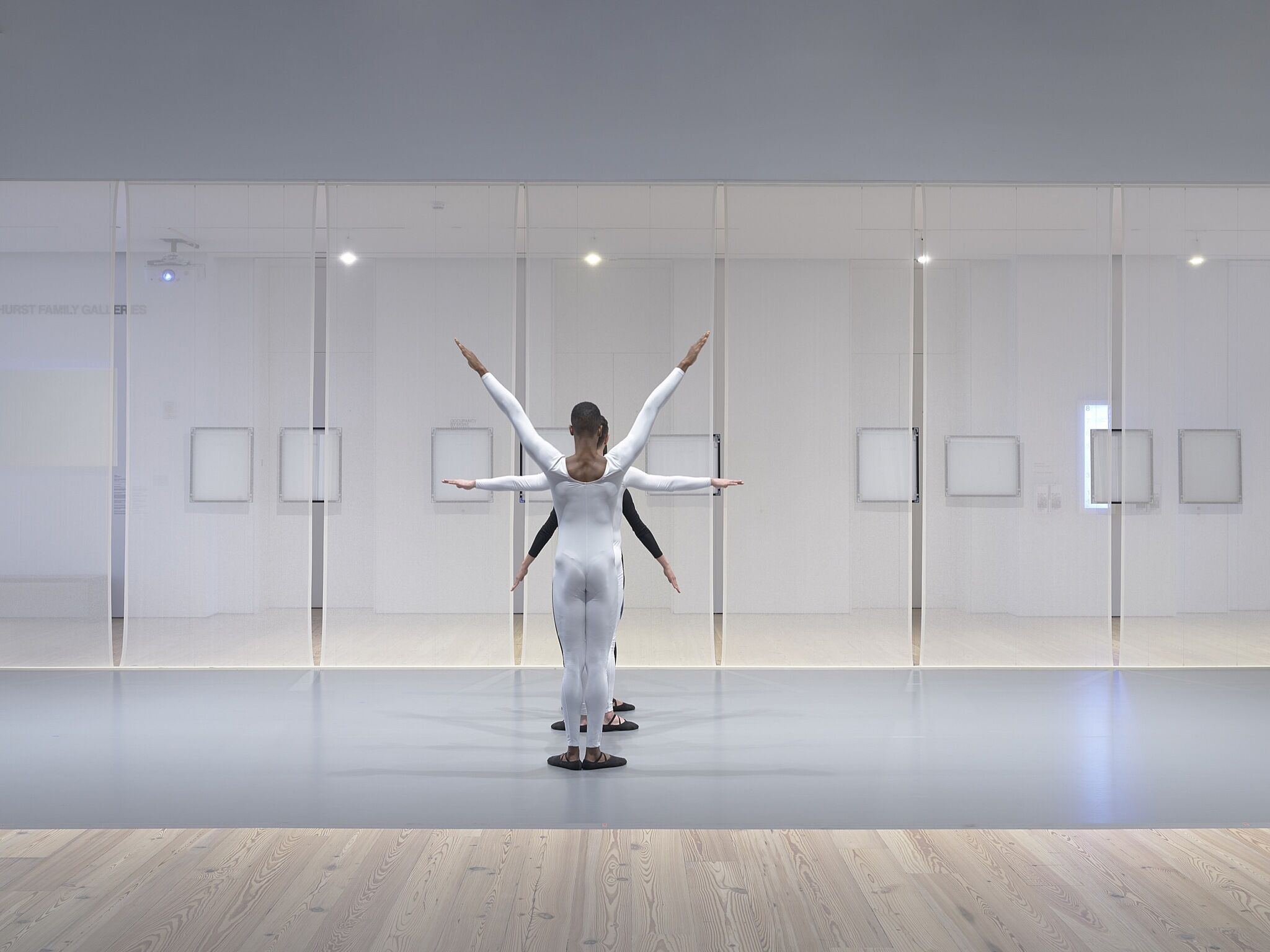 Three dancers perform in a gallery space.