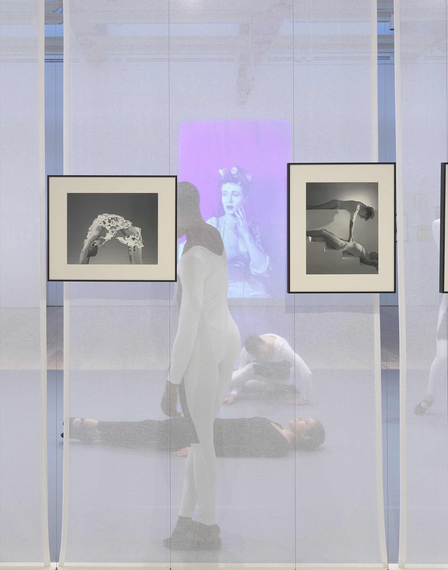 Four dancers perform behind a screen in a gallery space full of photos and video.