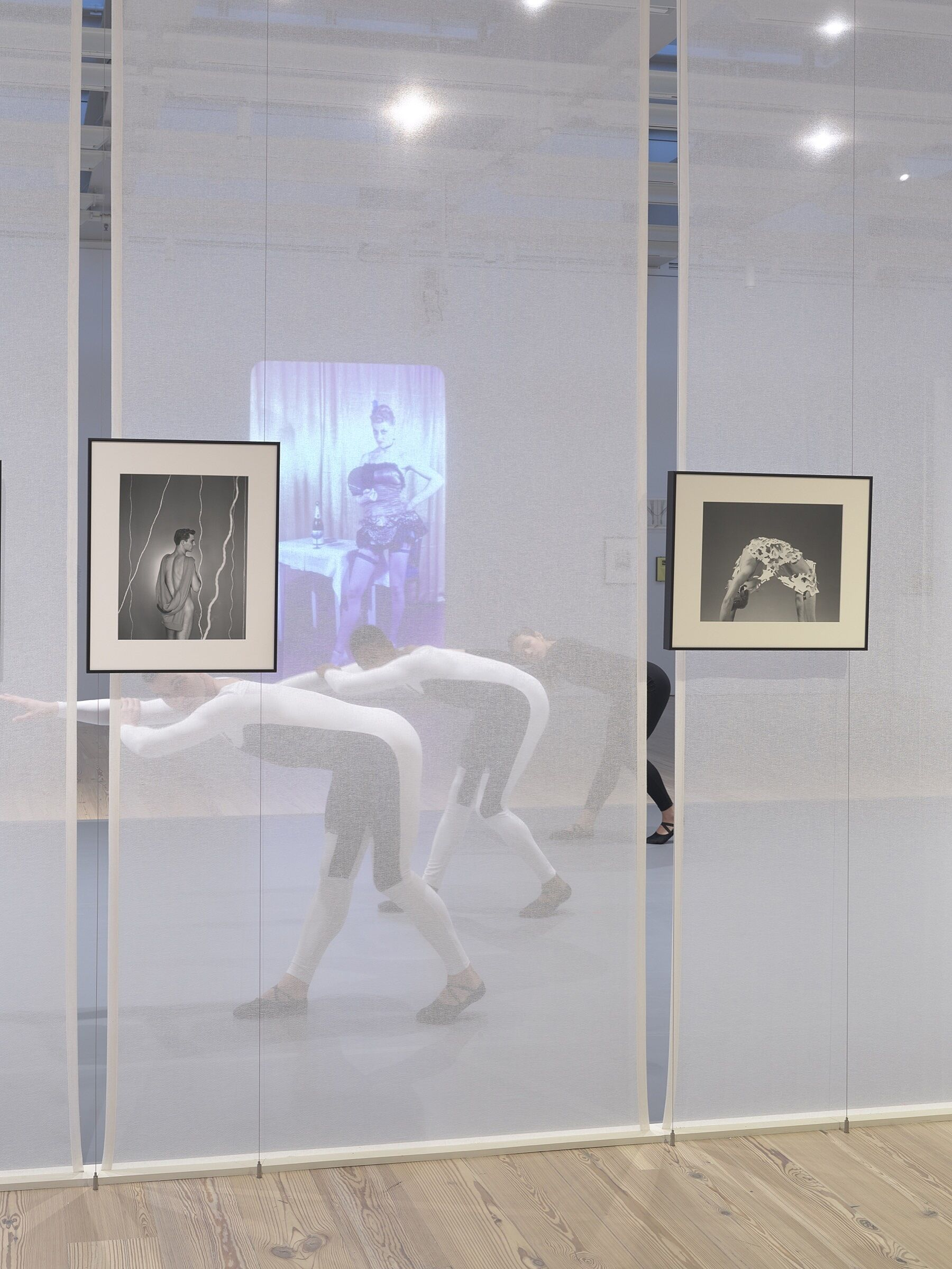 Three dancers perform behind a screen in a gallery space full of photos and video.
