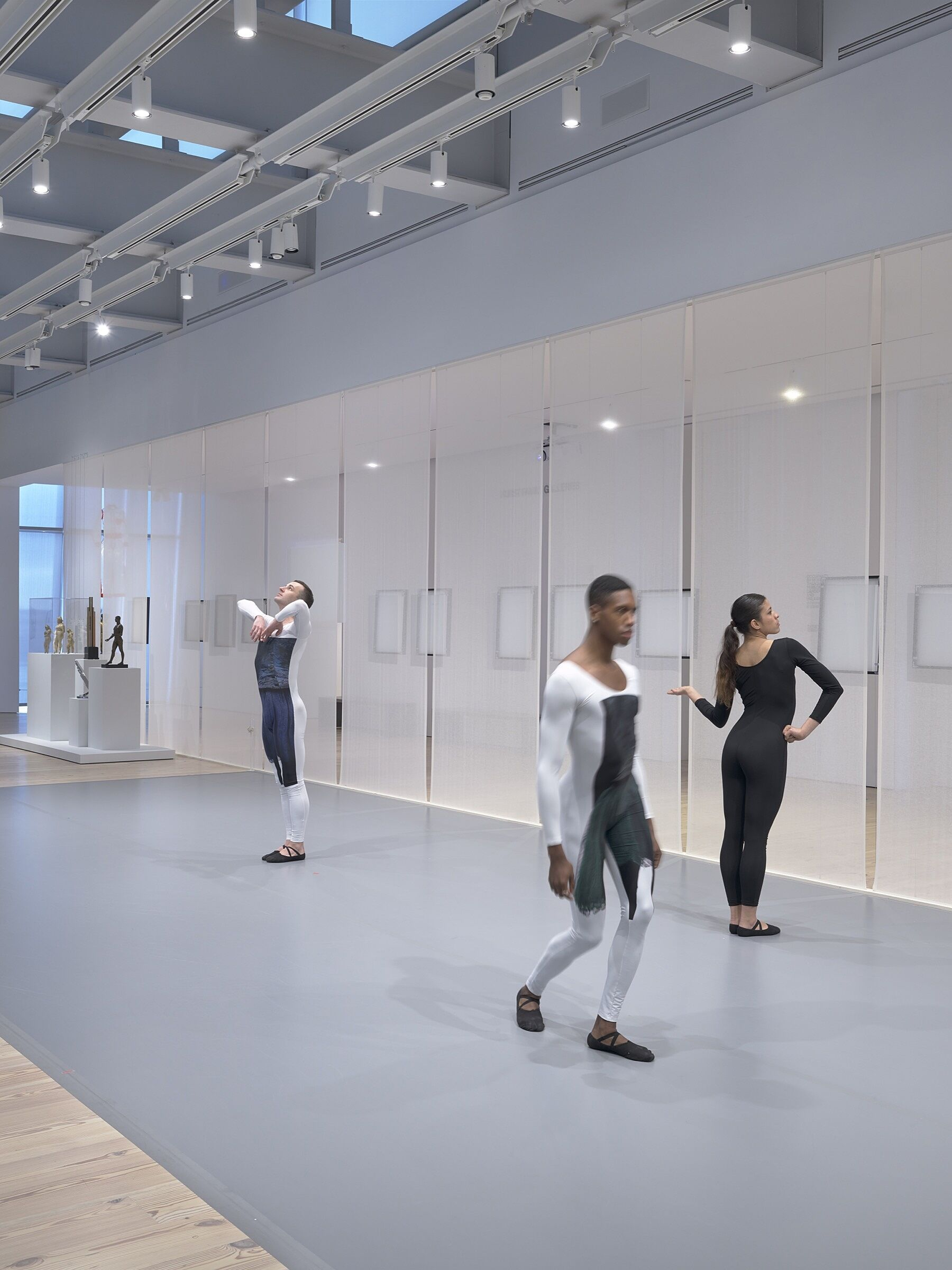 Three dancers perform in a gallery space full of photos and sculptures.