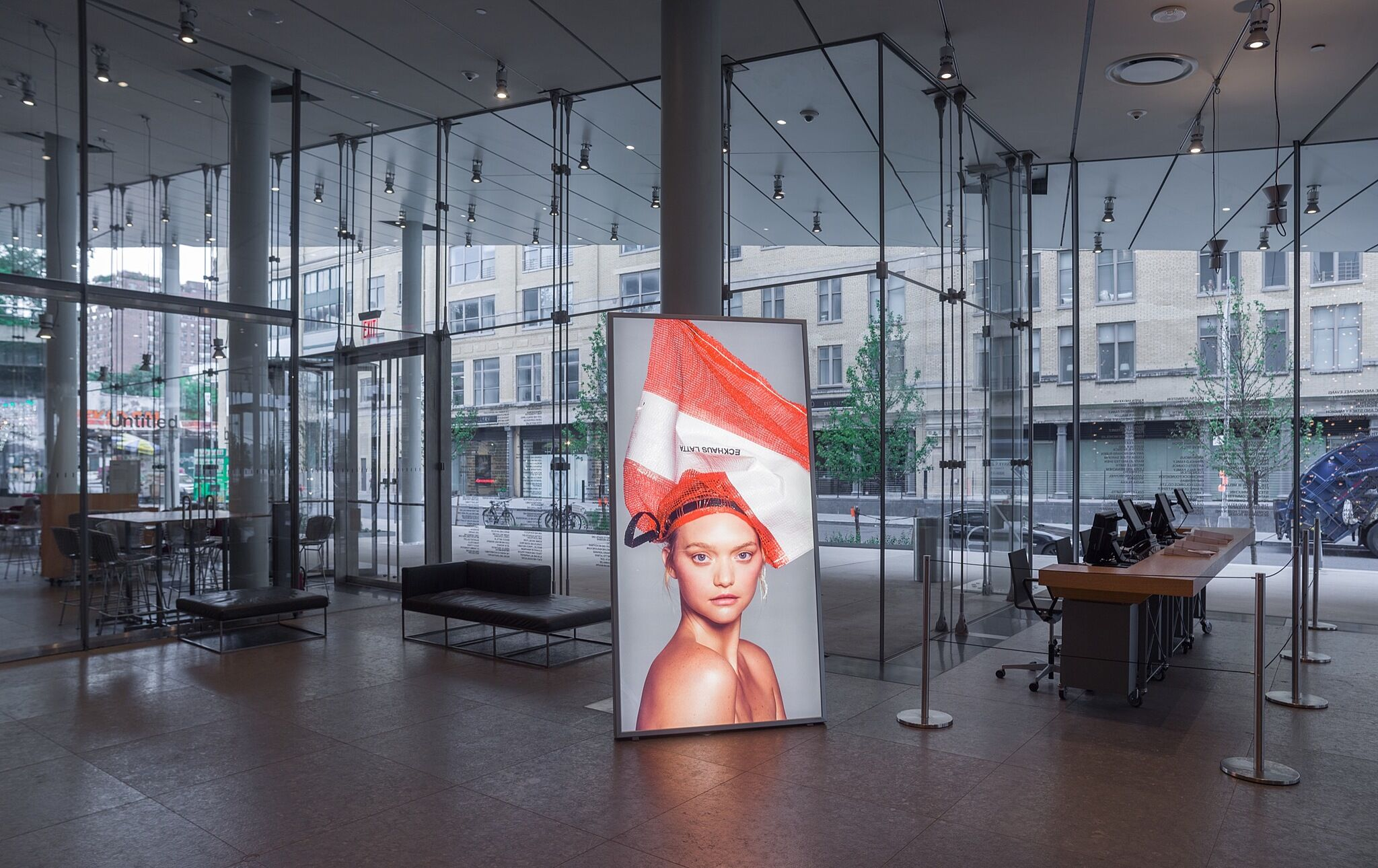 A lightbox photo of a blond model wearing a bag on their head in the Whitney lobby.