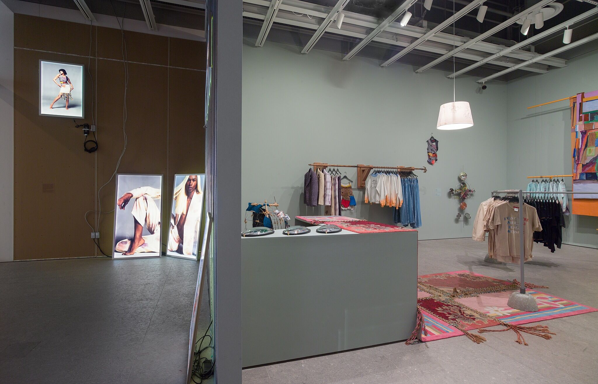 Two gallery spaces: one with lightbox photos of models and the other a faux retail shop.