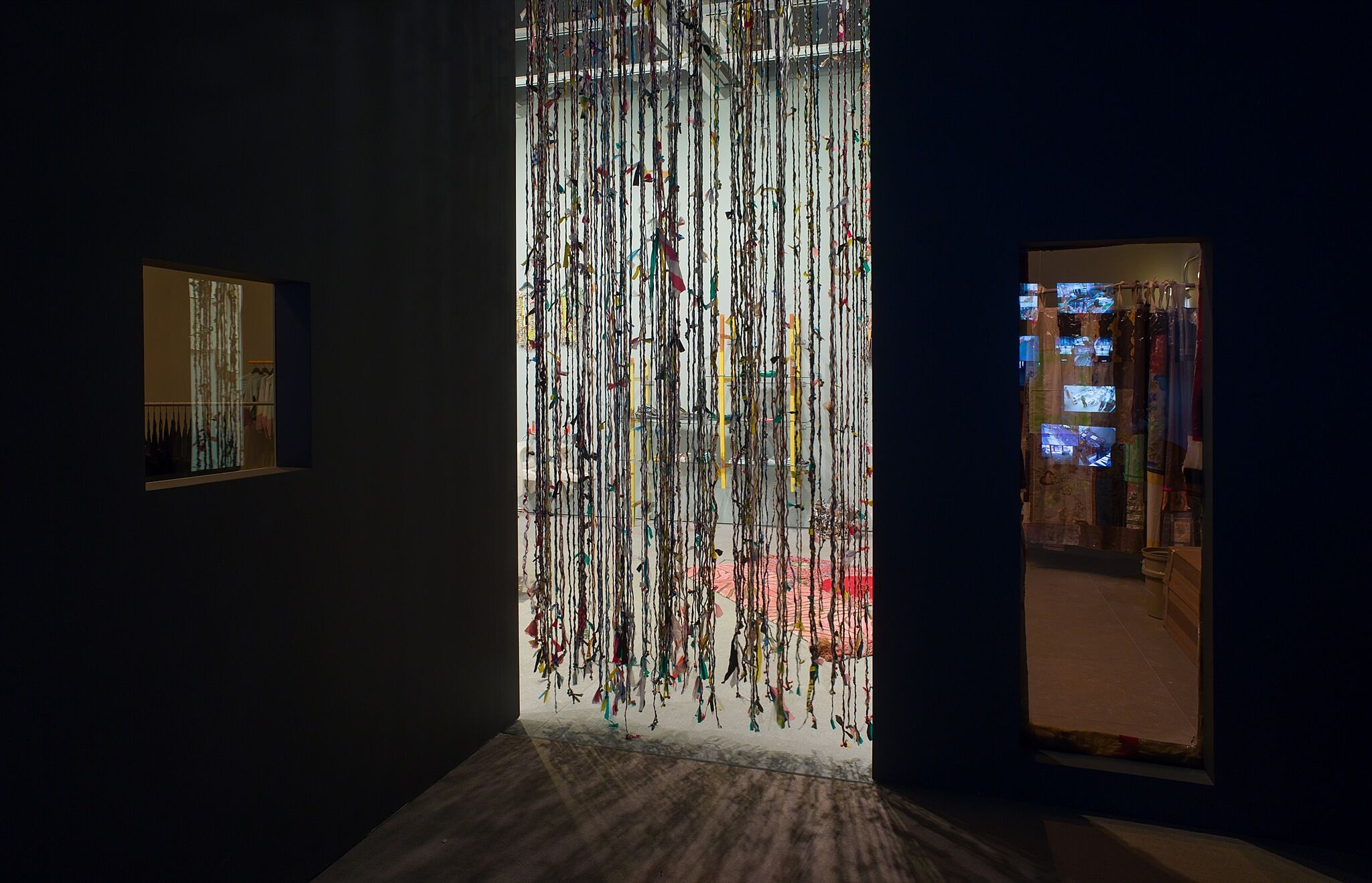 A dimly lit gallery space made to look like a dressing room with a beaded curtain.
