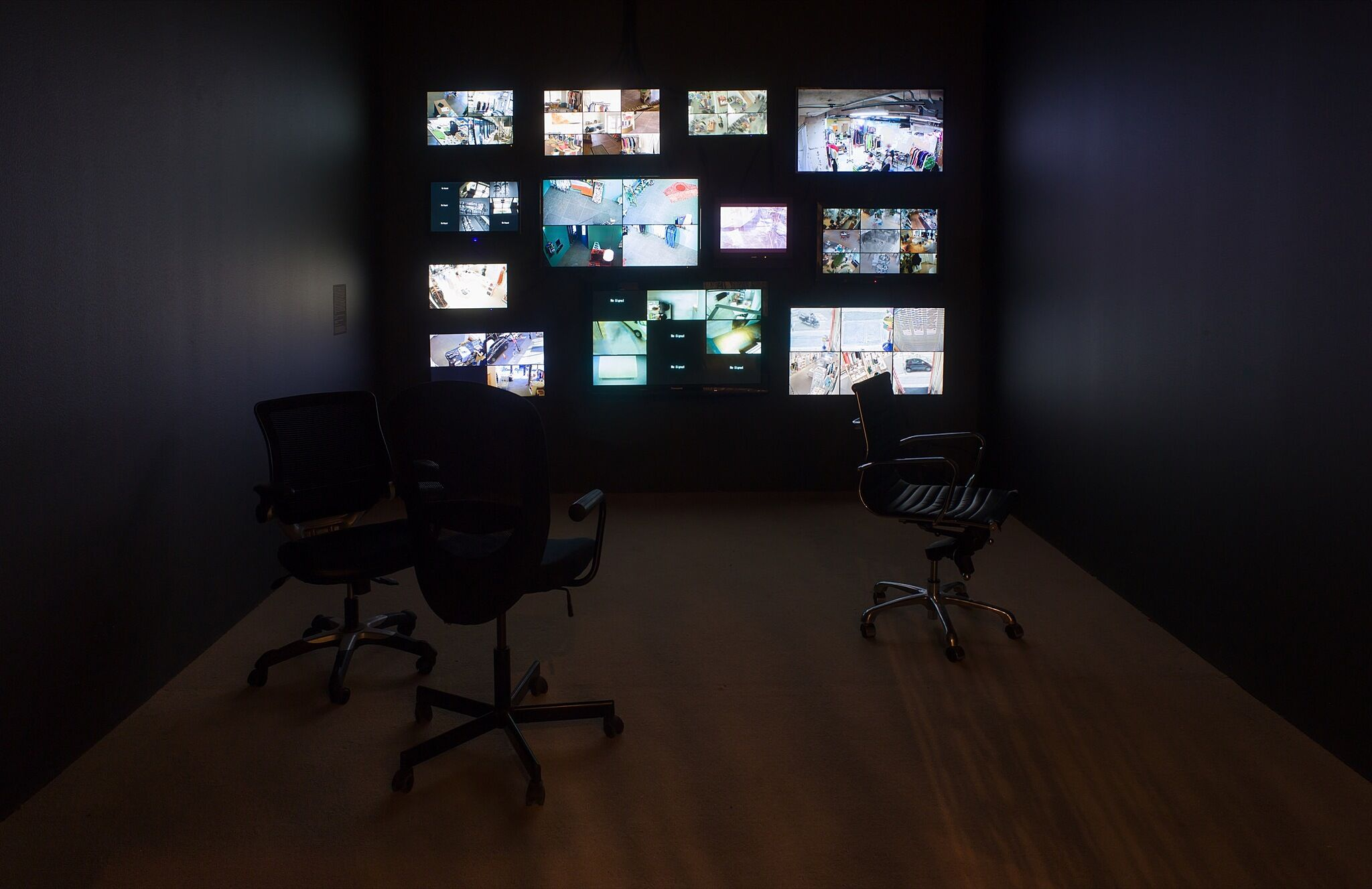 A dark gallery space with many video monitors playing surveillance footage.