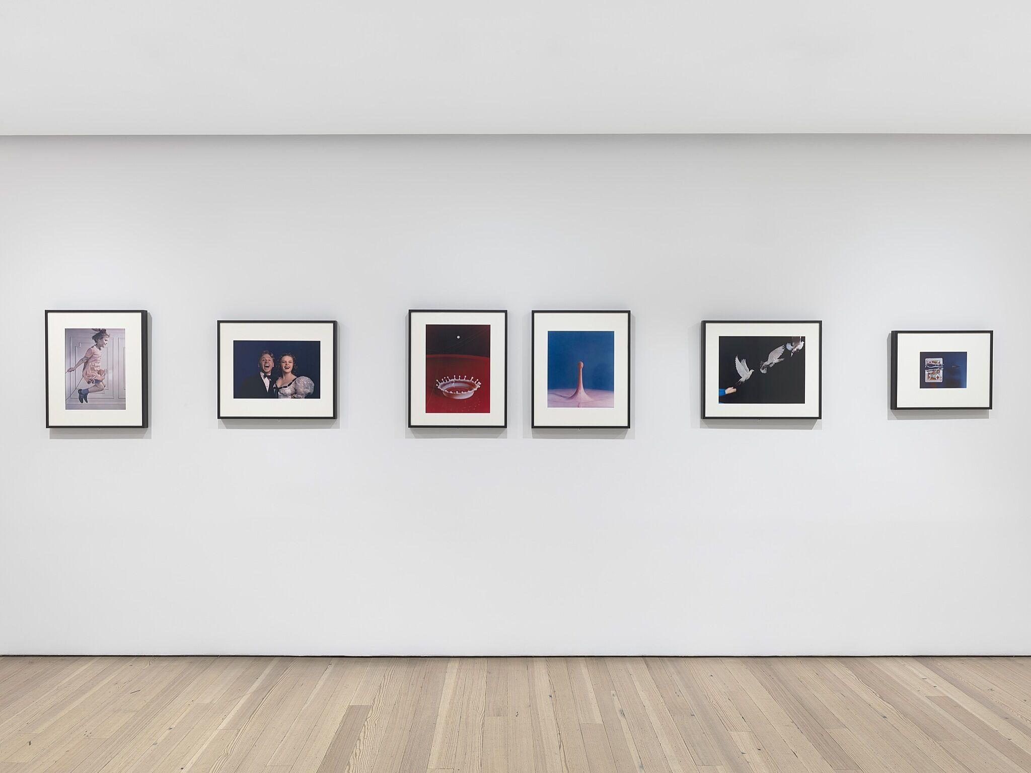 Various photographs framed on a gallery wall.