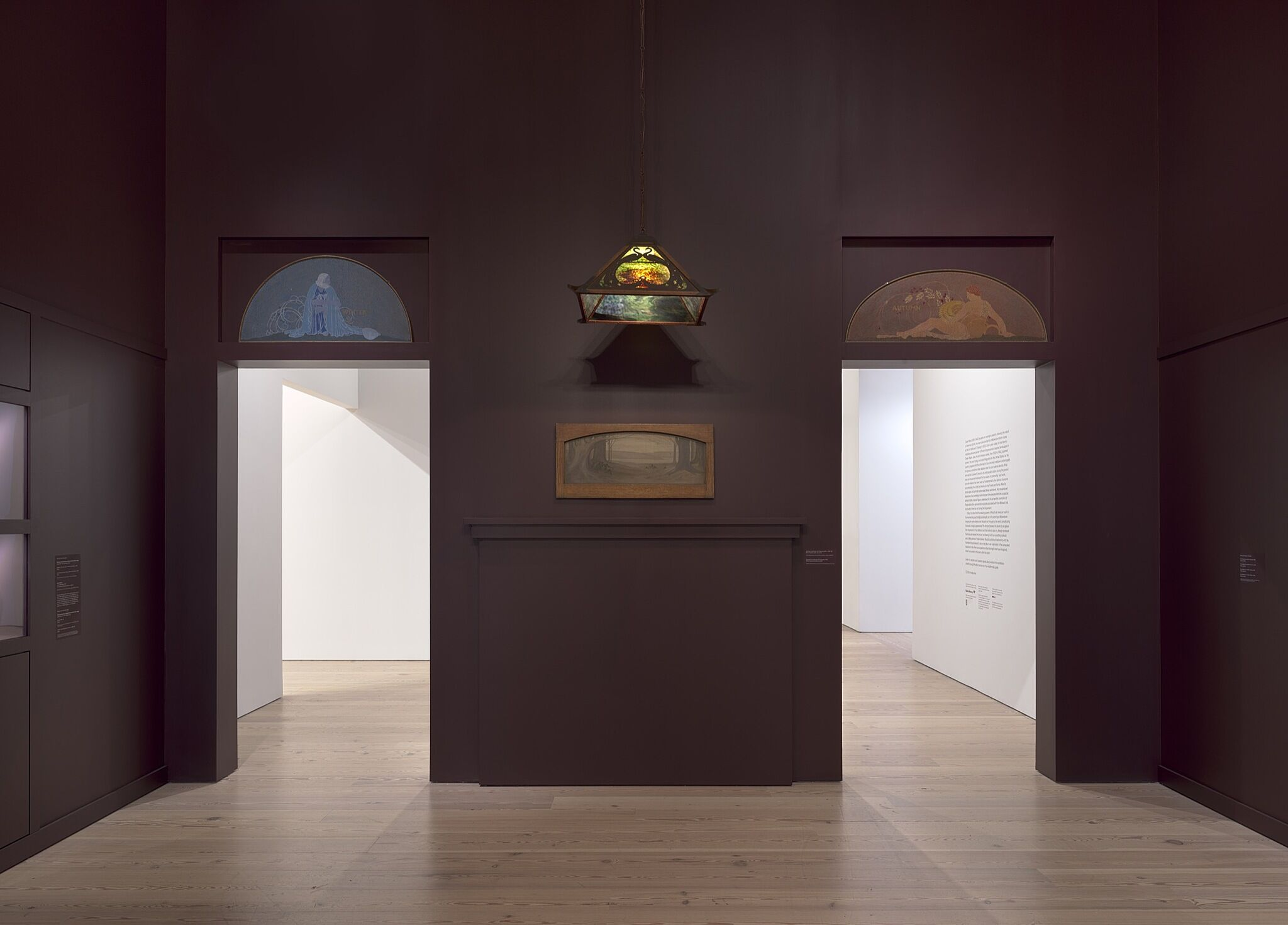 A photo of a gallery space with paintings on the wall and above the entryways.