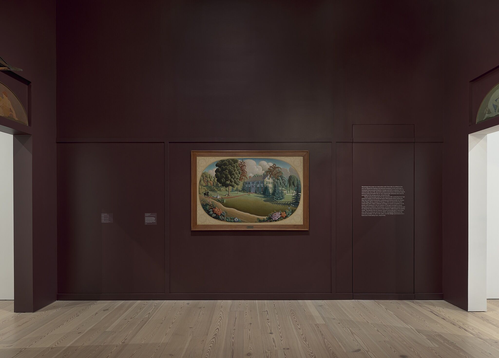 A painting of a landscape and building on a deep purple gallery wall.