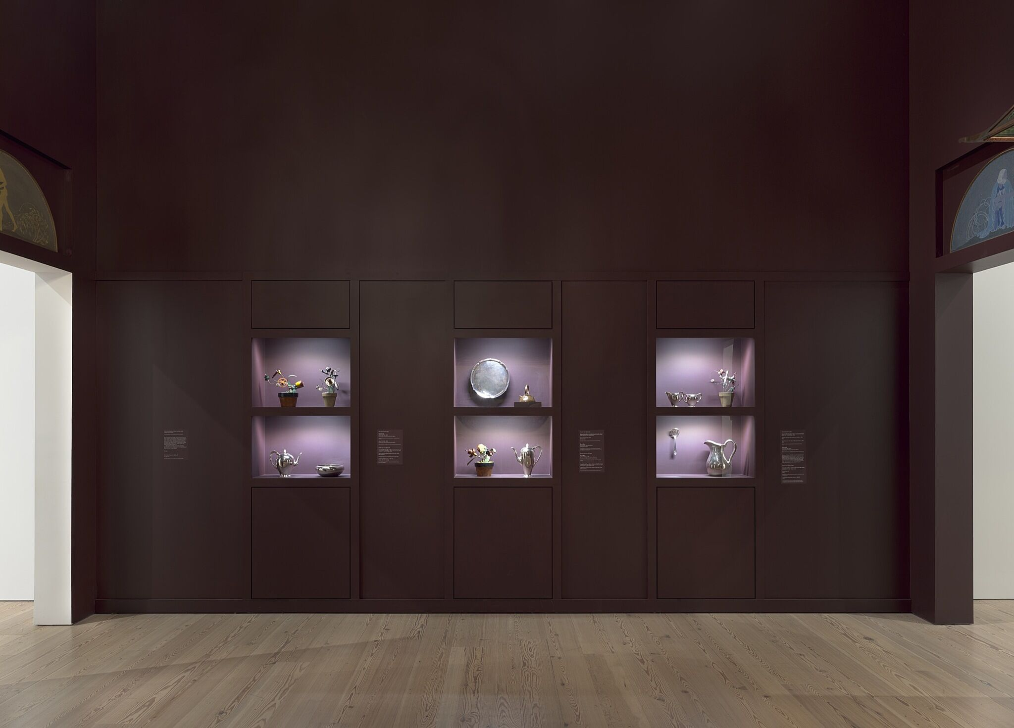 A series of dishes and silverware in display cases on a gallery wall.