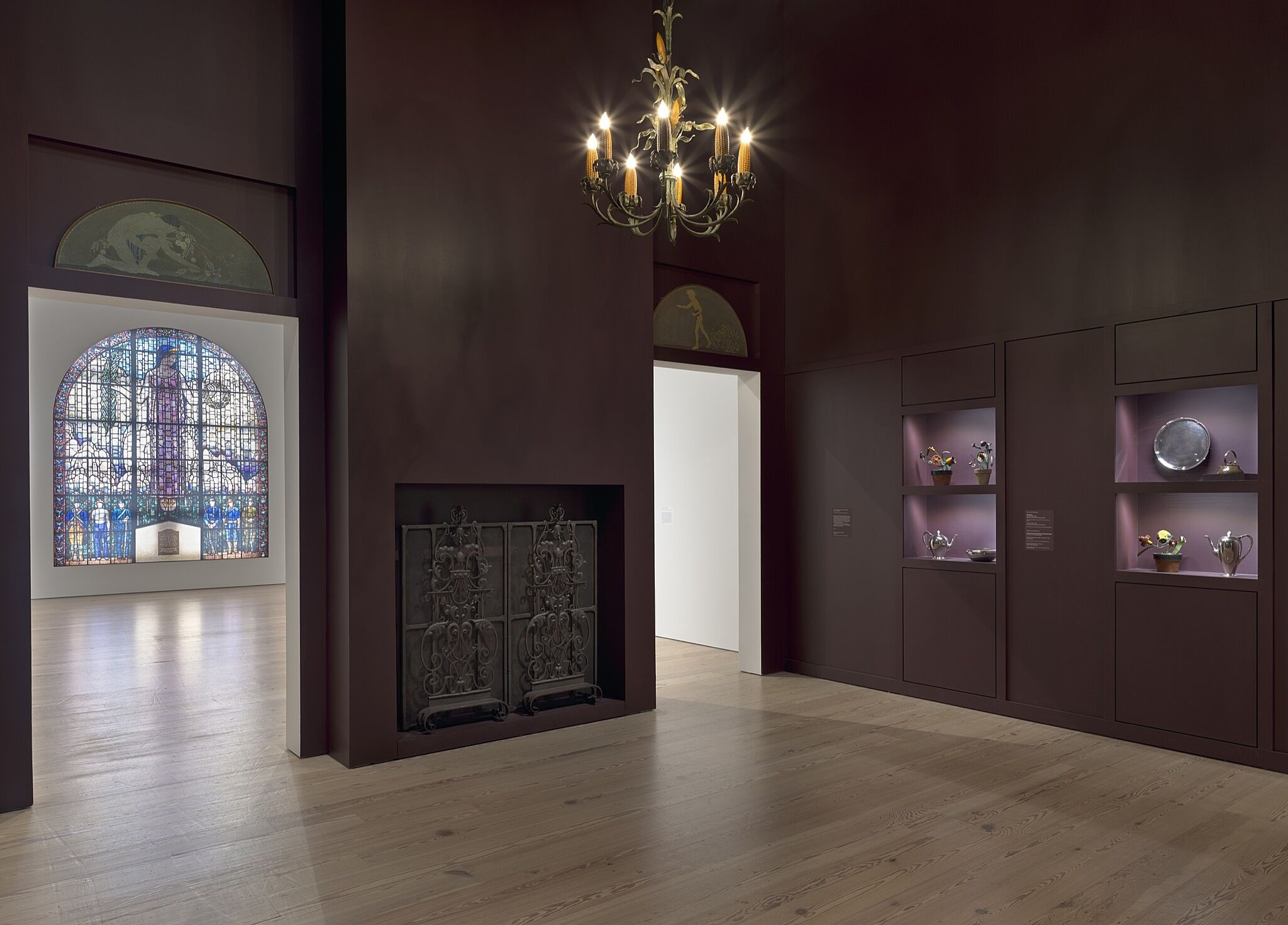 A gallery space with paintings, various dishware sets, and a stained glass window.