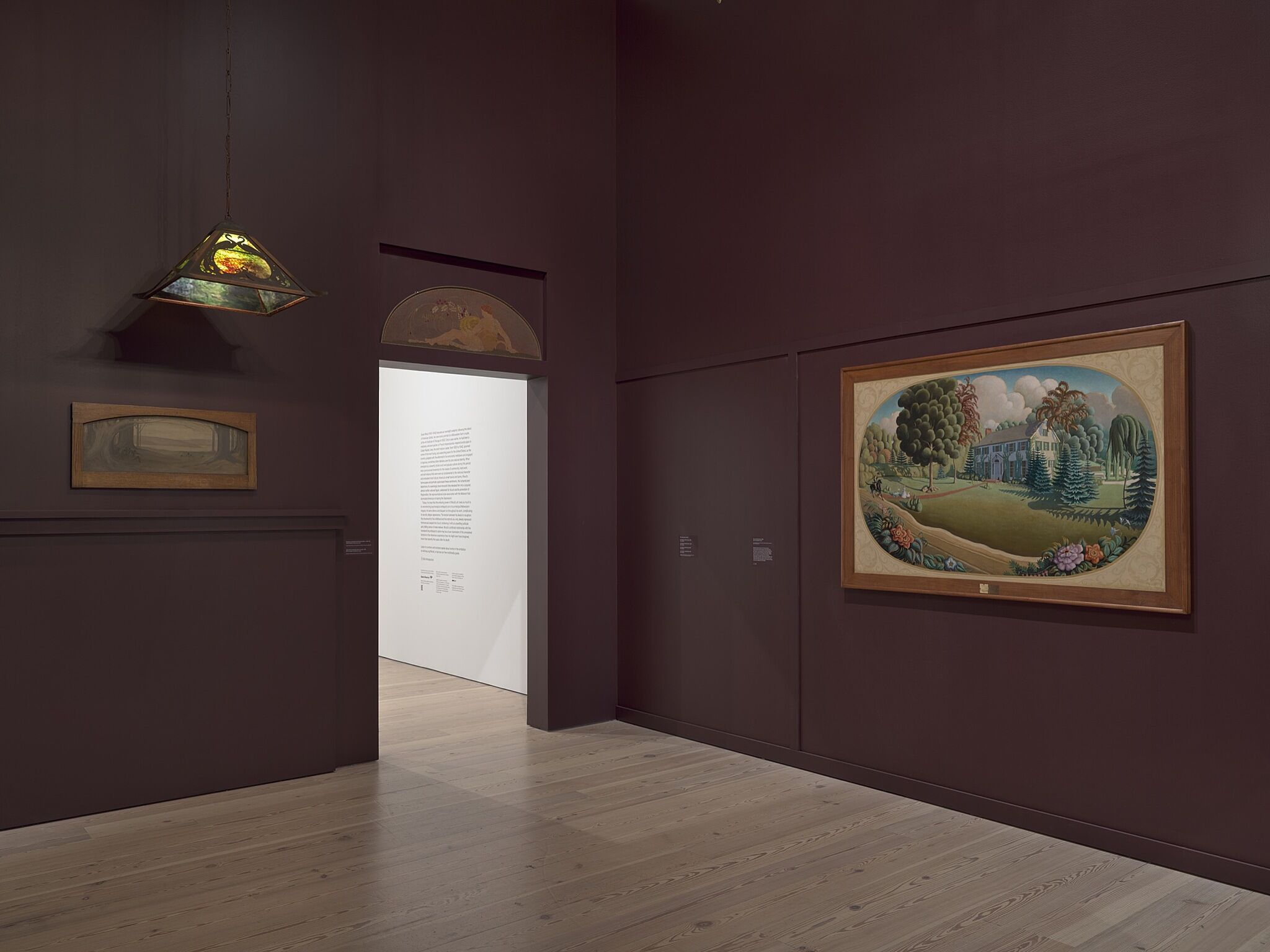 A gallery space with paintings and an ornate ceiling light.