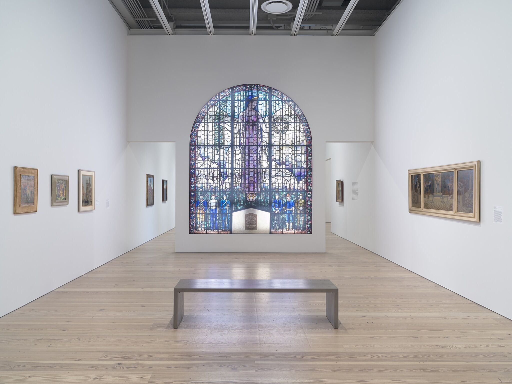 A gallery with a large stained glass window and various paintings.