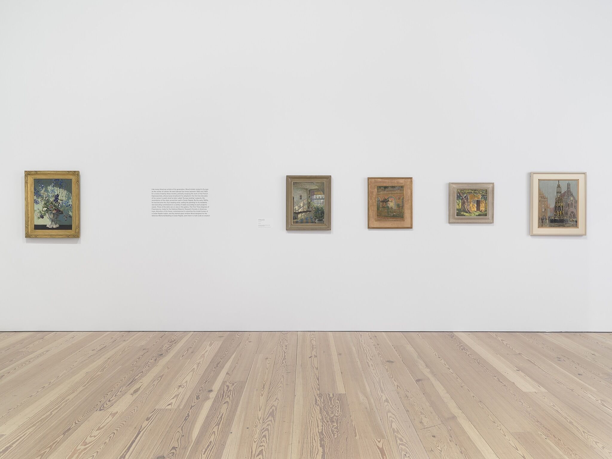 Five small vertical paintings on a white gallery wall.
