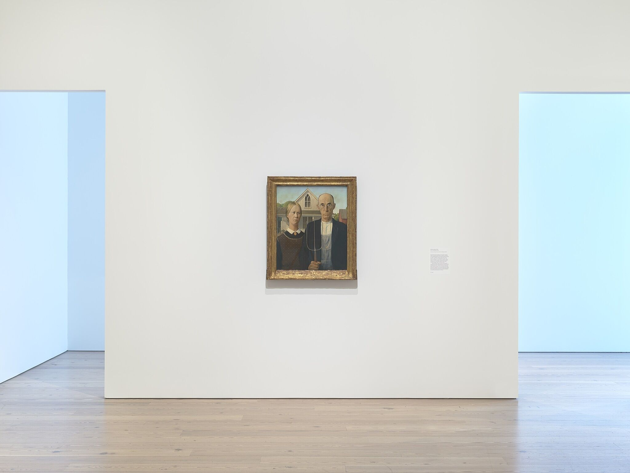 A painting of two farmers in a white-walled gallery.