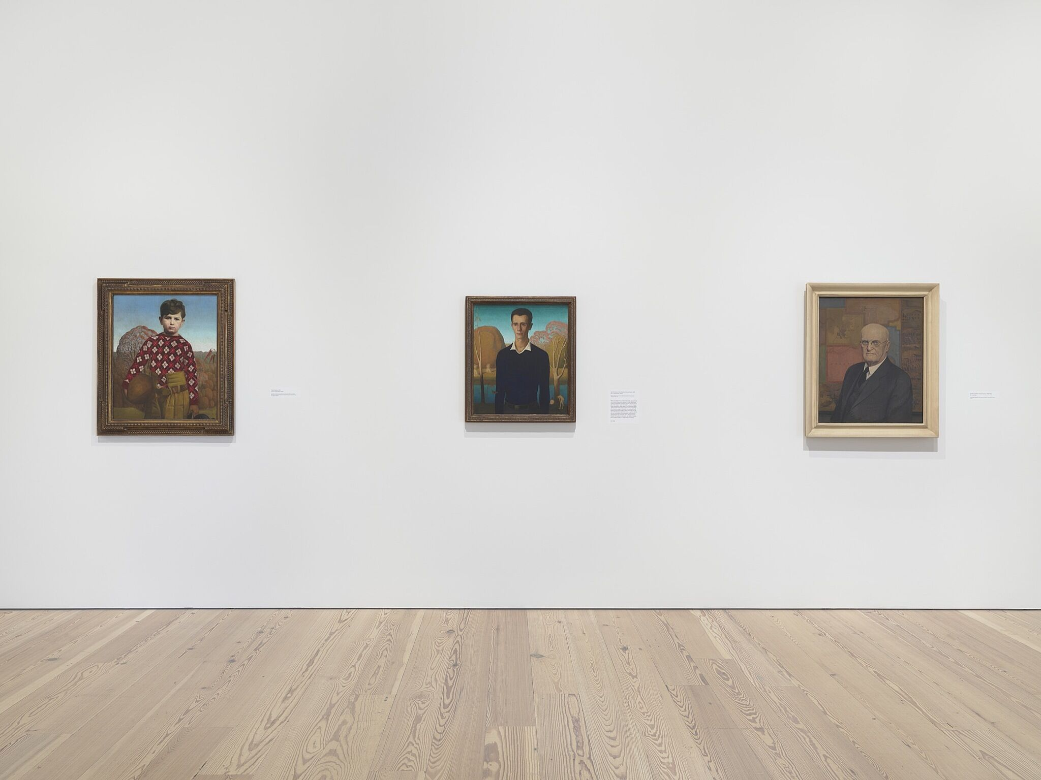 Three paintings in a white-walled gallery.