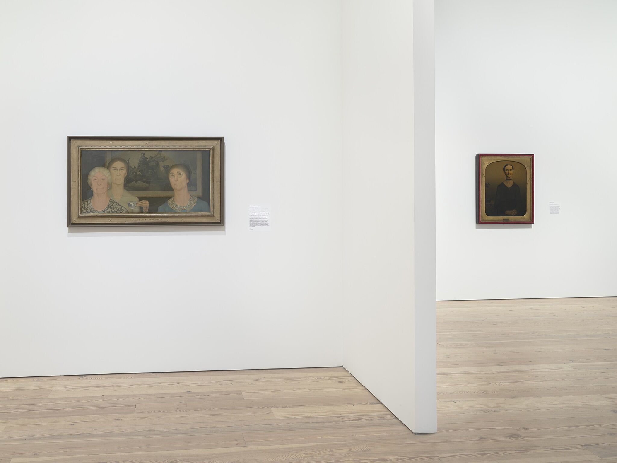 Two paintings in a white-walled gallery.