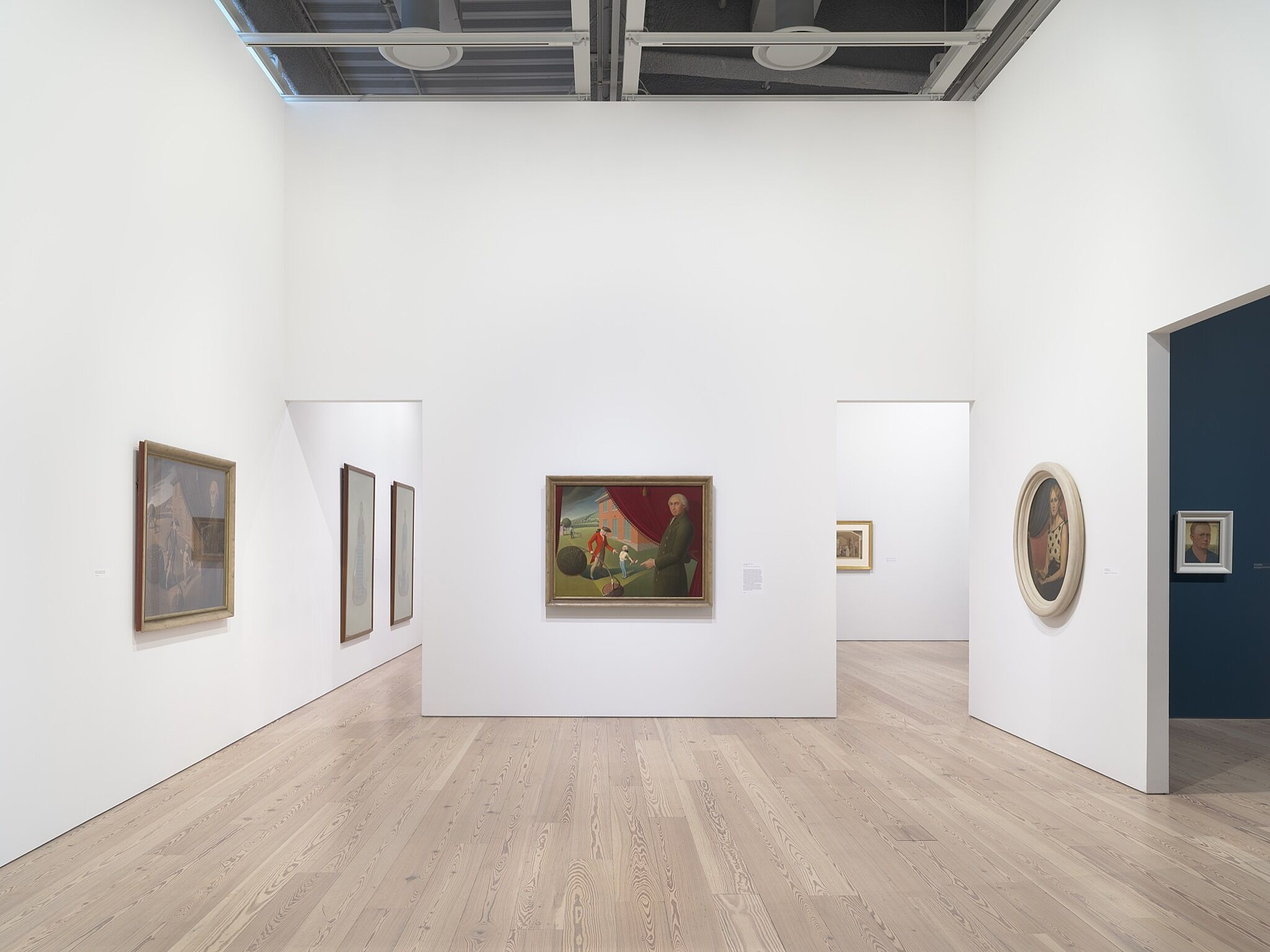 A photo of the Whitney galleries with various paintings.