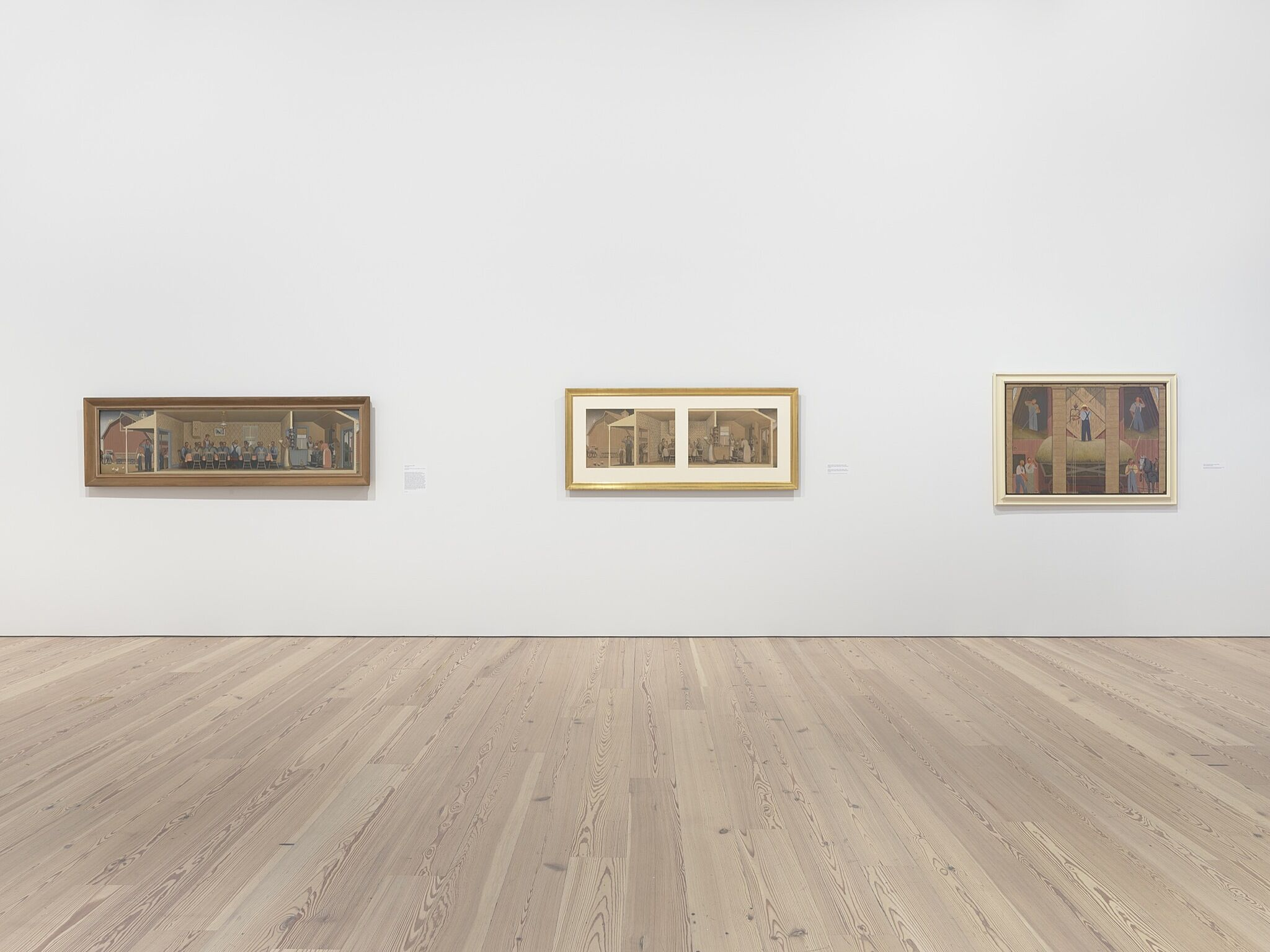 Three paintings on a white wall in a gallery.