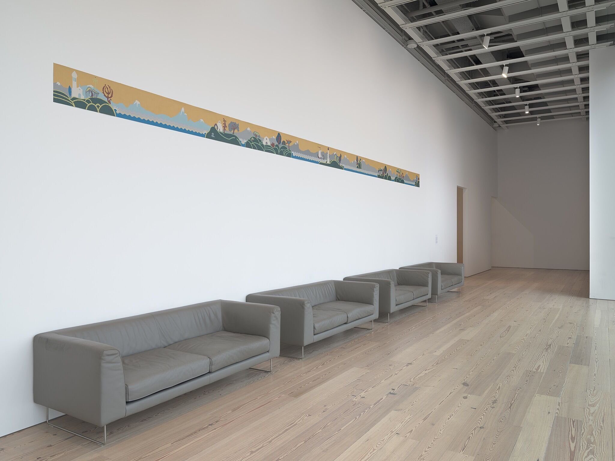 A long painting above a couch in a gallery looking out towards large windows.