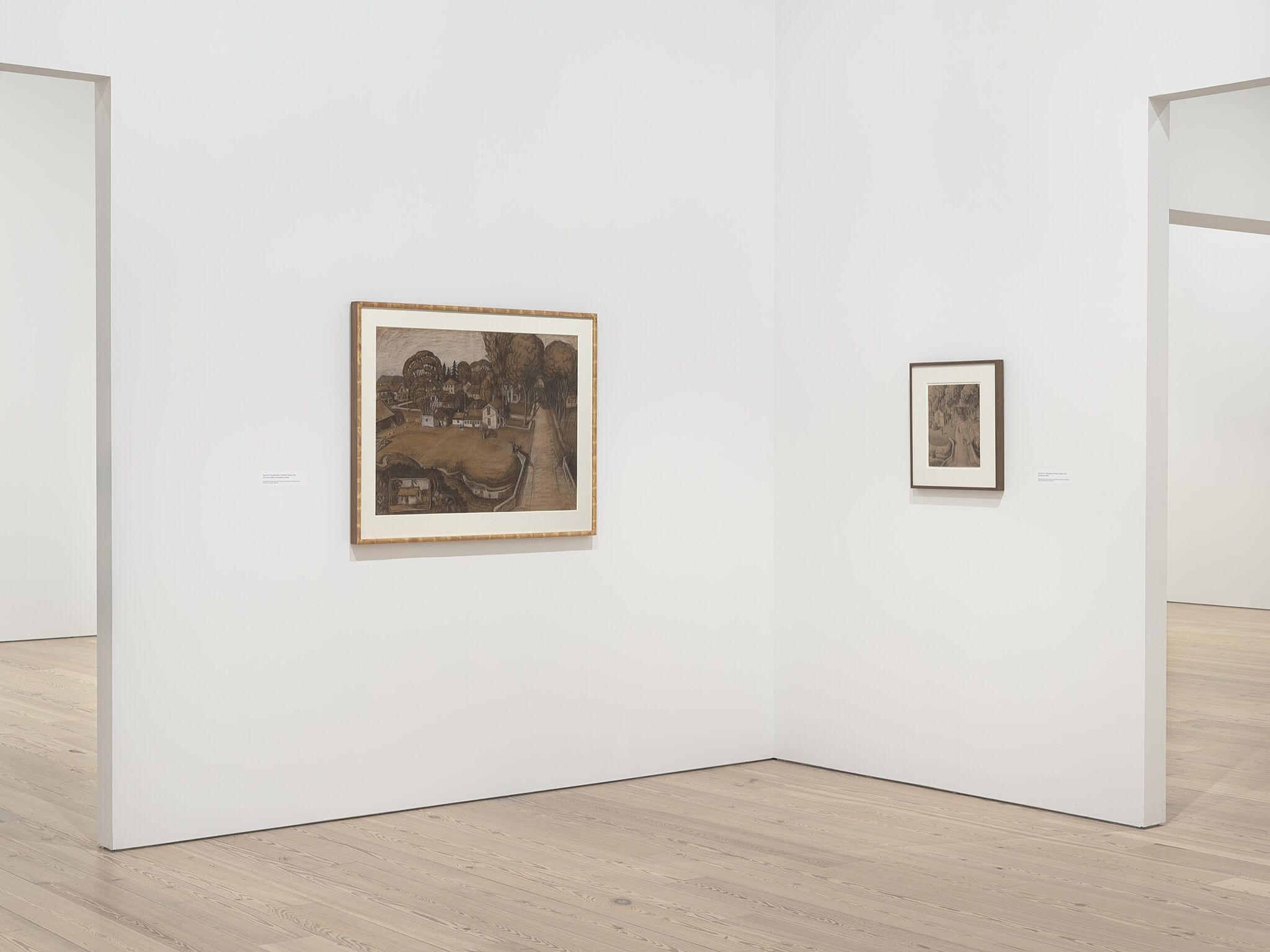 Two paintings in a white walled gallery.