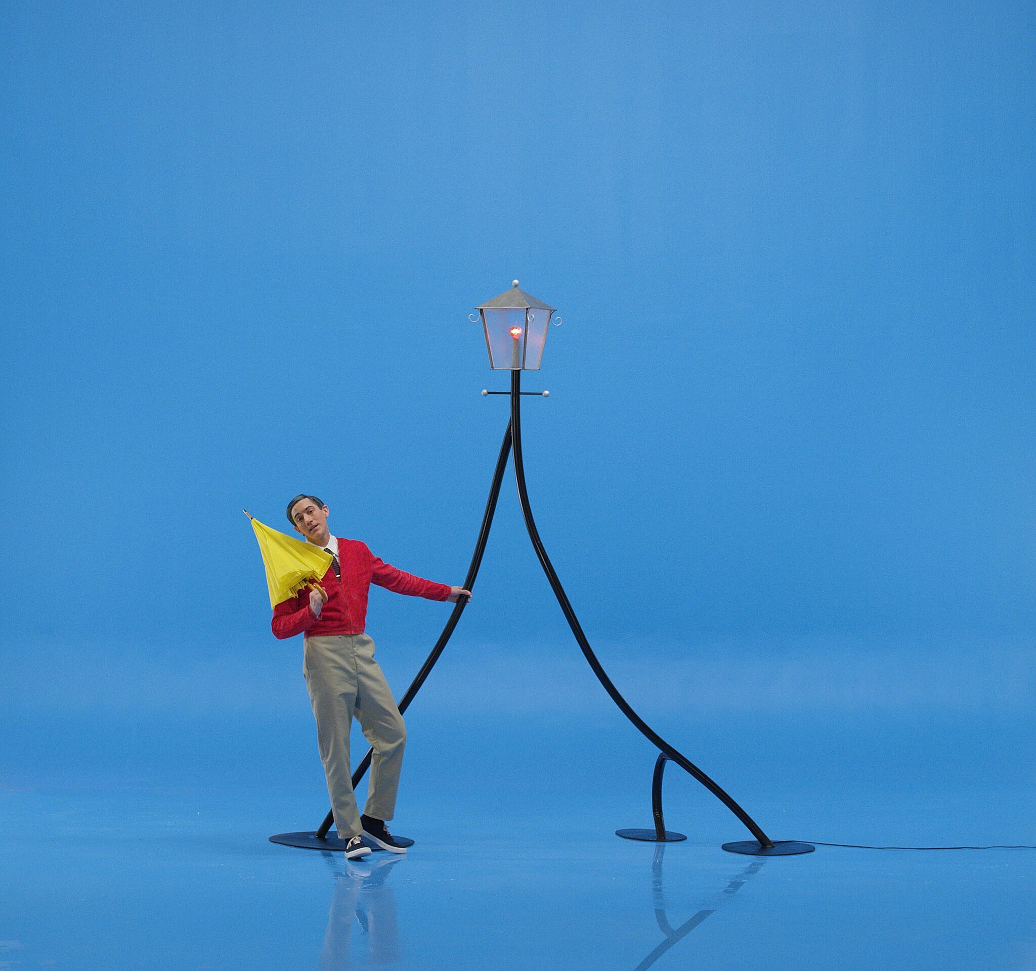 A man dressed like Mr. Rogers hangs off of a streetlamp against a bright blue background.