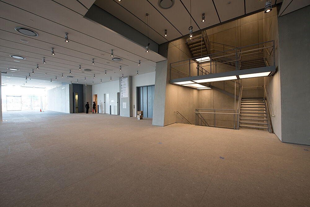The Griffin Hall Gallery, empty, in daylight at the Whitney Museum of American Art. The image shows the room designed by Renzo Piano, with windows far to the left and a staircase toward the right.