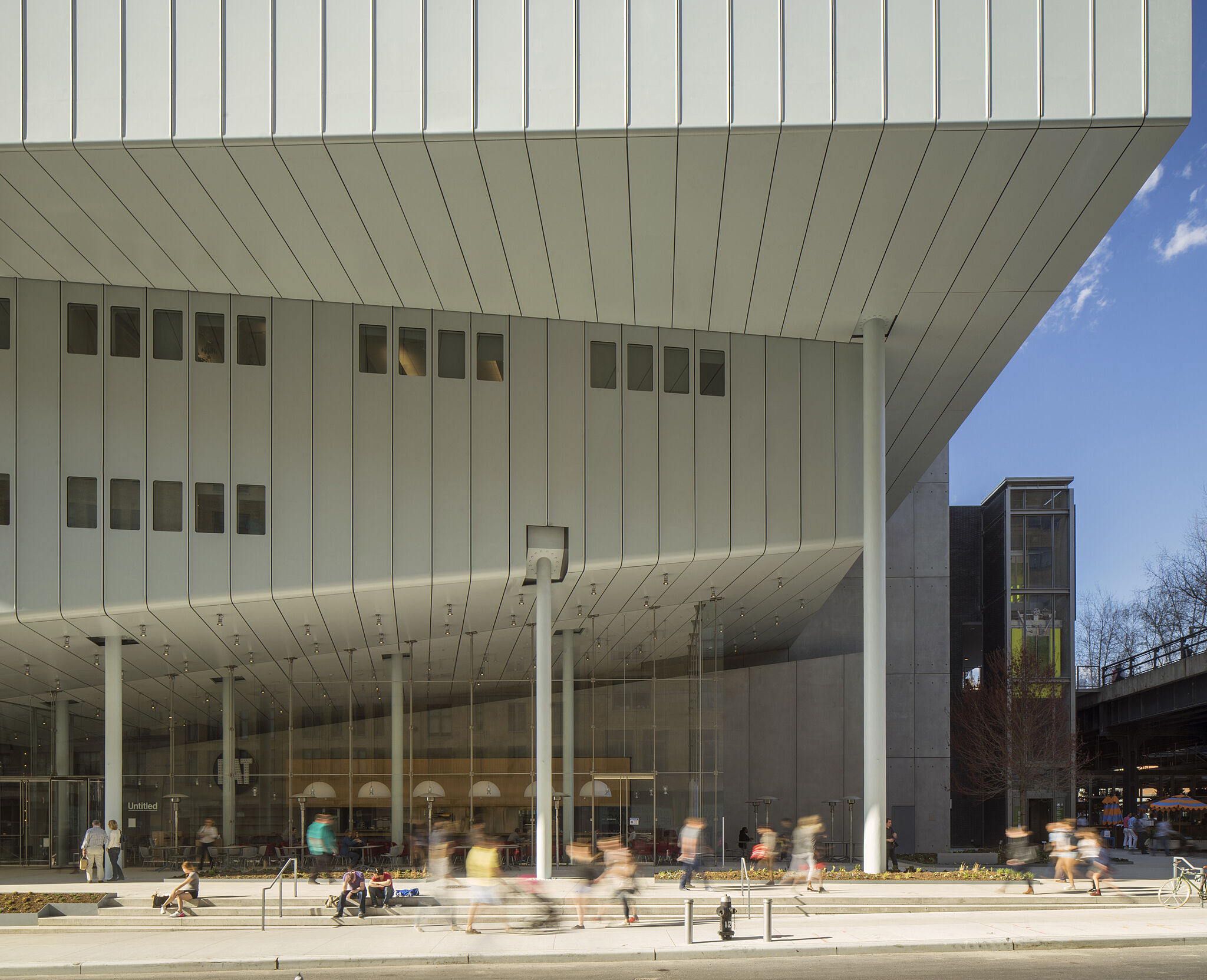 Bright white or grey building, the Whitney Museum of American Art, pictured with time lapsed people in front of the museum columns on a bright day.
