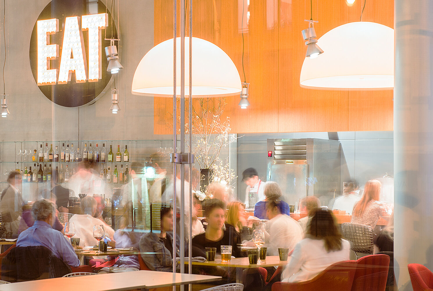 A lot of people seated in a time lapse, eating at a restaurant in front of a sign that says EAT, with bright lights and an orange wall.