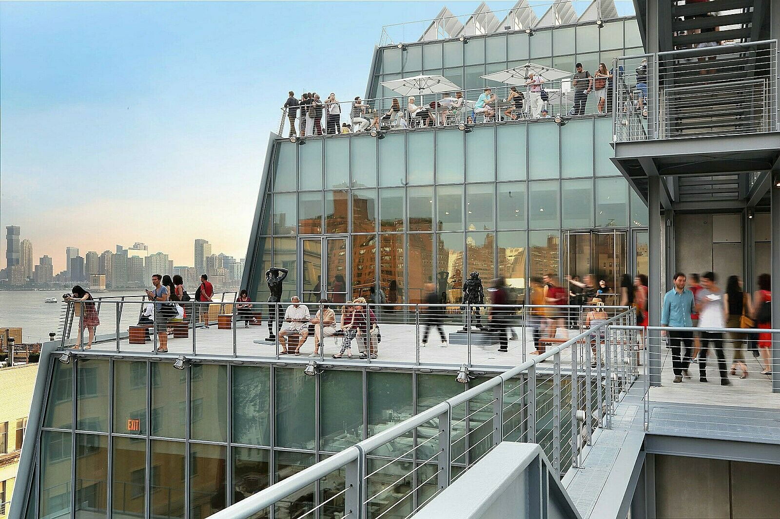 Many people explore the patios of the Whitney Museum of American Art on a bright day in a time lapsed photo. The reflections of the large glass windows appear in front of a view of the city and river in New York City.