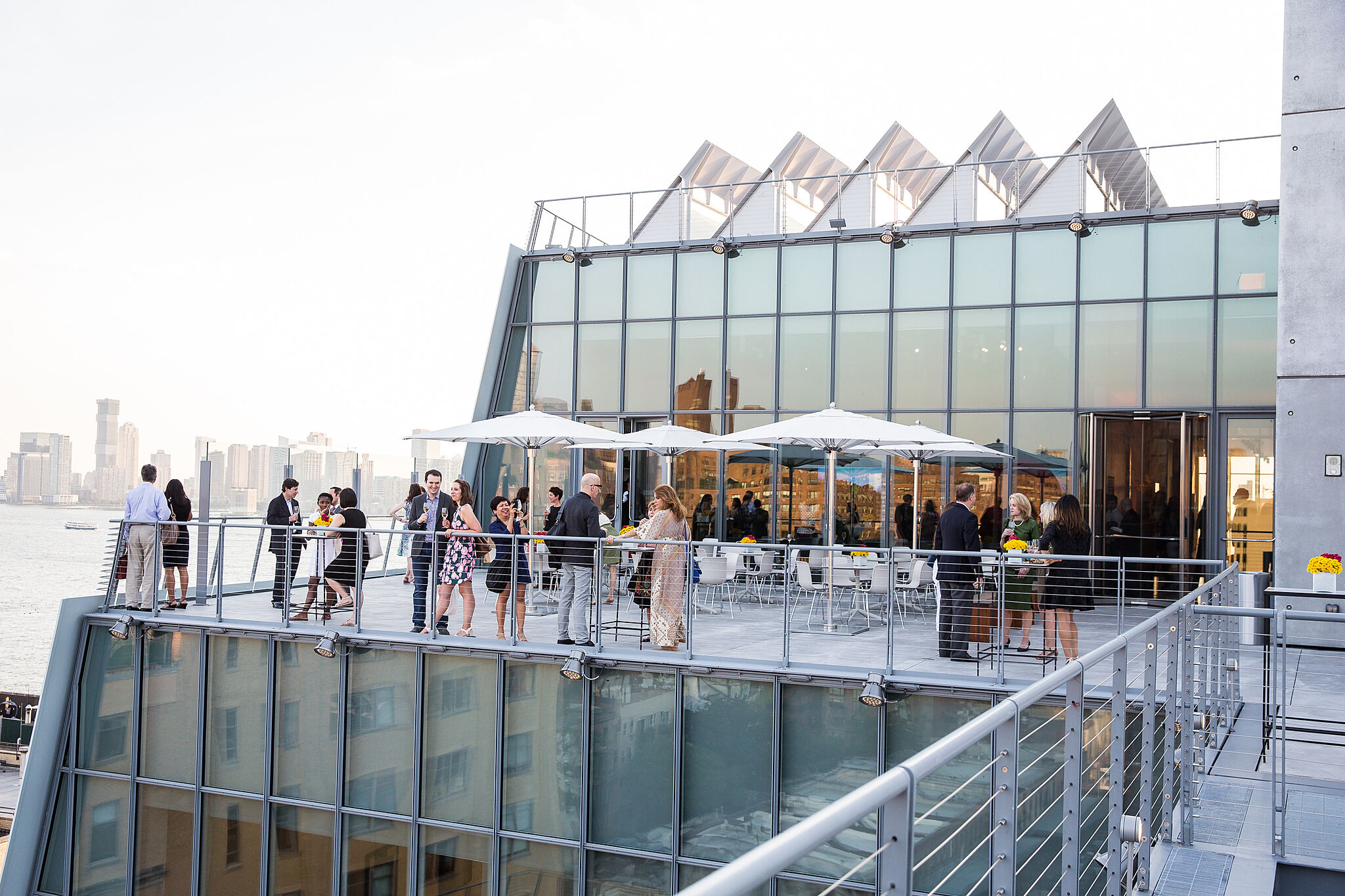 Museum guests in semi formal evening attire mingle on the top patio of the Whitney Museum of American Art outside of the Studio Cafe on a bright and beautiful day.