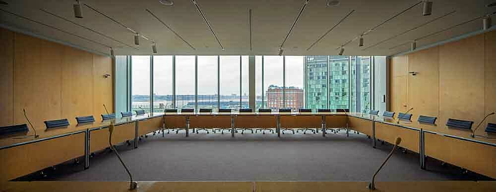 The Trustee Room of the Whitney Museum of American Art, a bright, large and empty room, with large windows with a view of New York City.