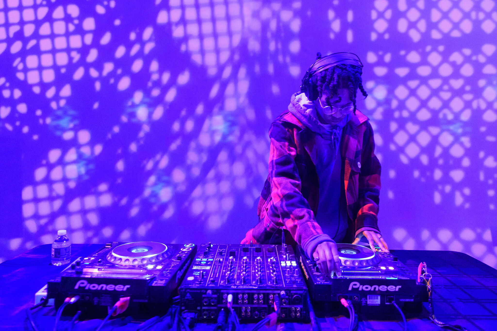 A DJ playing in a purple-lit room.