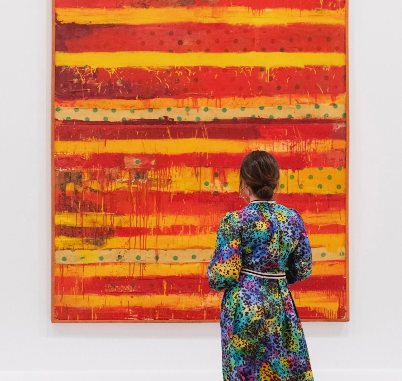 A woman in a printed dress stands in front of a painting.