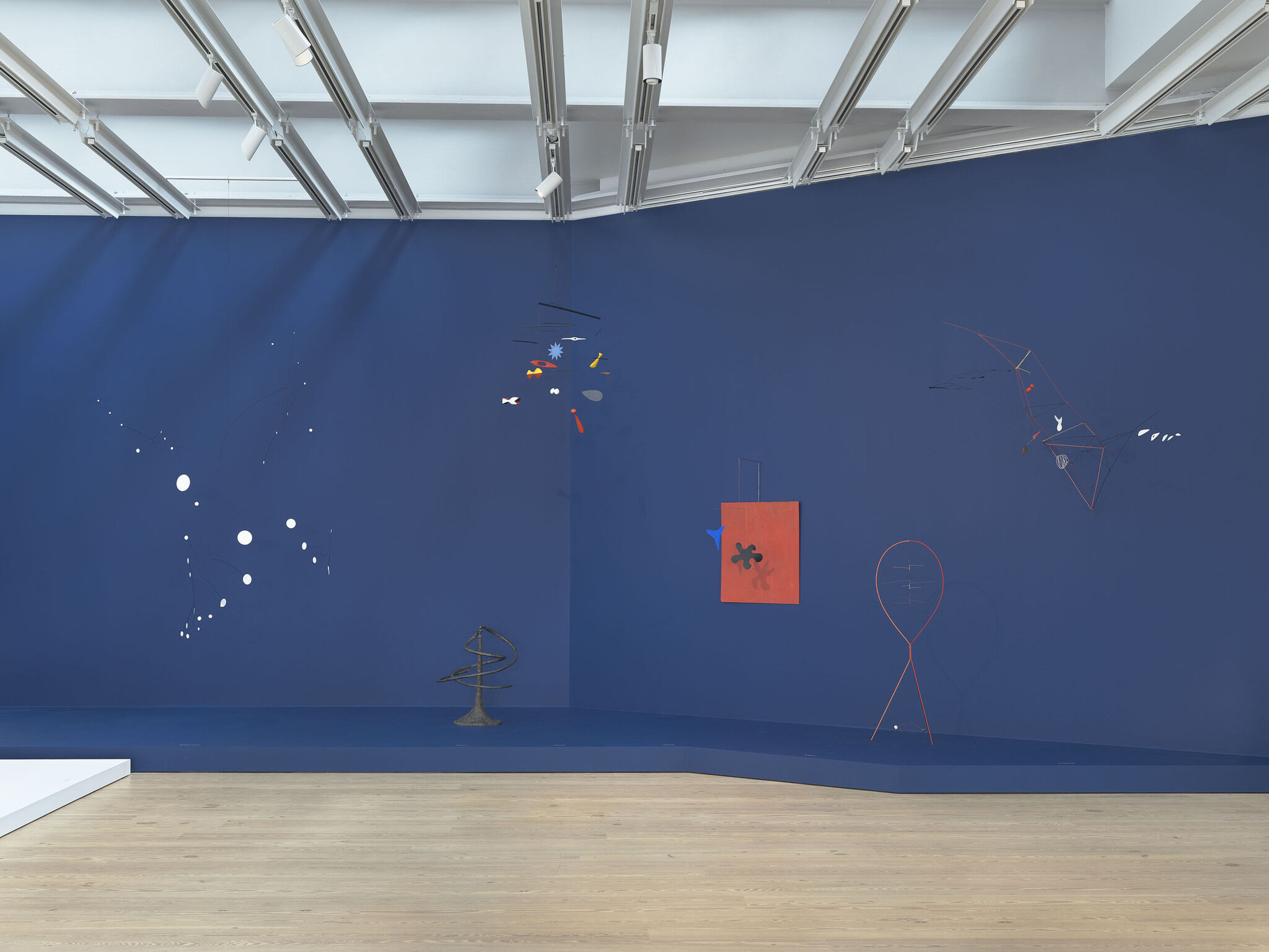 A gallery view of a dark blue wall in the exhibition Calder: Hypermobility
