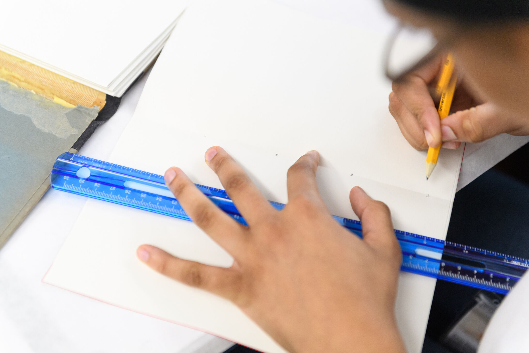 A young person's hand holds a ruler over a page as they use a pencil