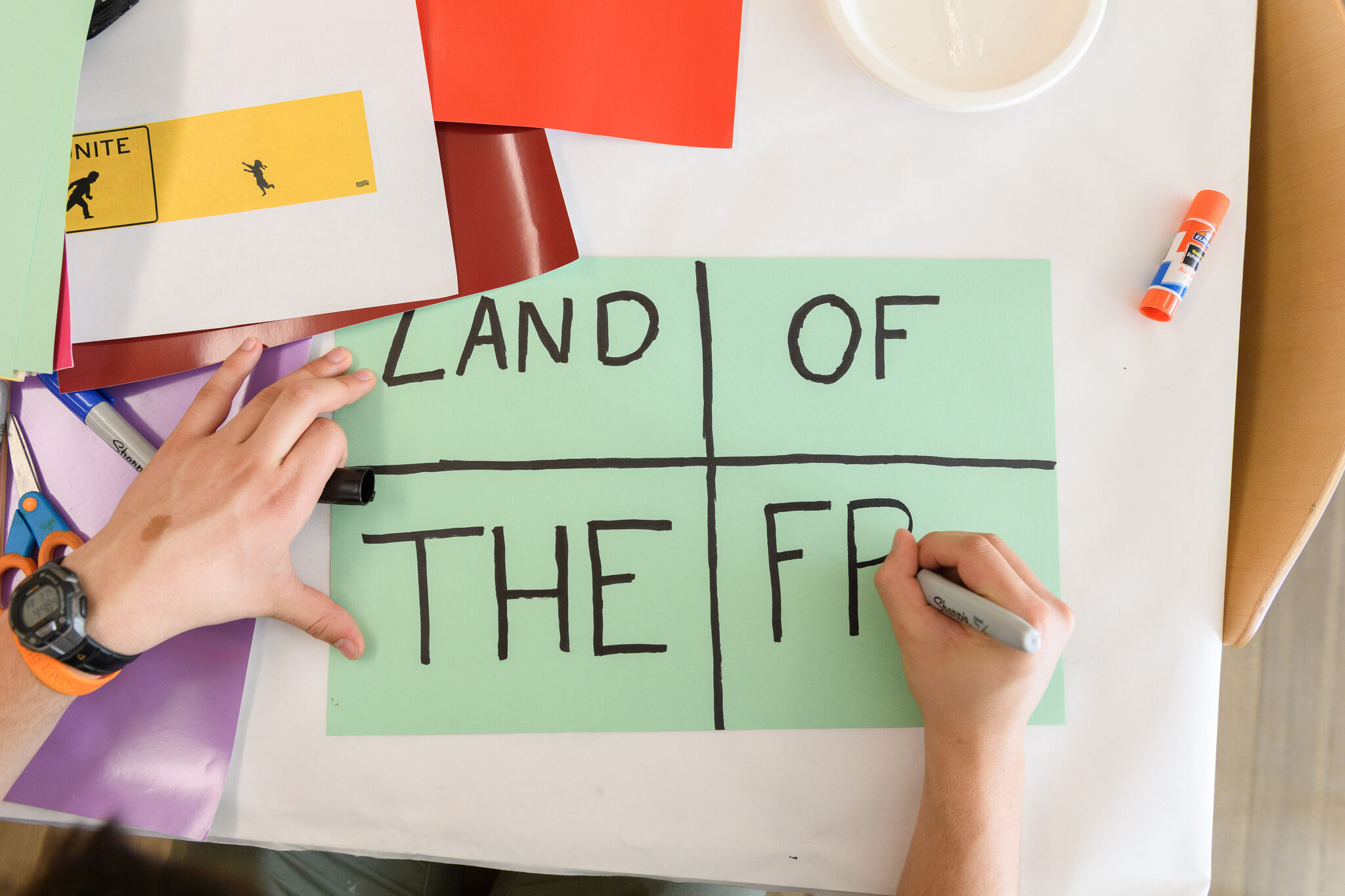 """Someone is writing on a green paper on a table. The sheet says, """"Land of the free."""""""