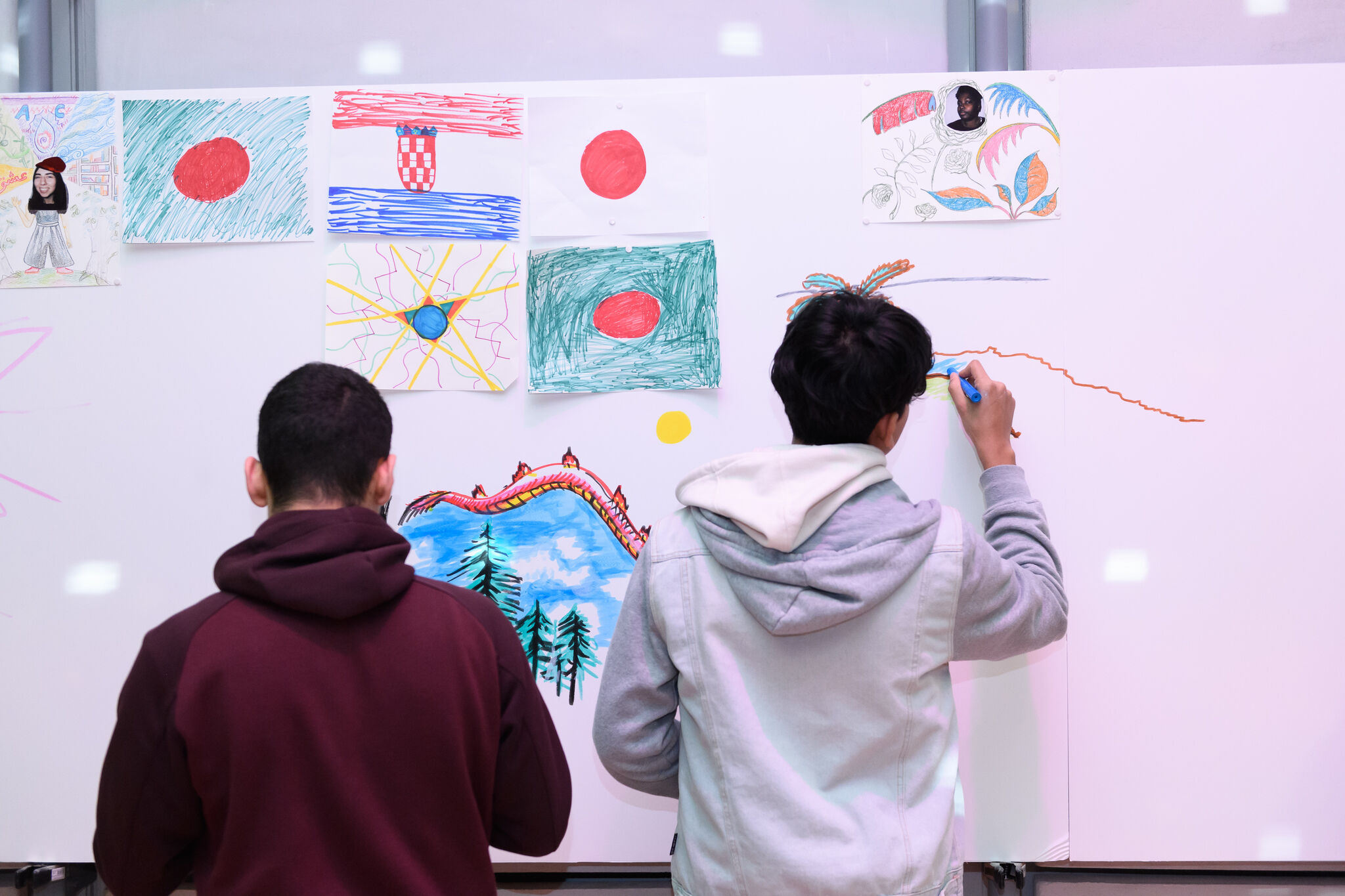 Two teenage people with short hair and hoodies are drawing with markers on a white board. The white board also has various drawings pinned to it.