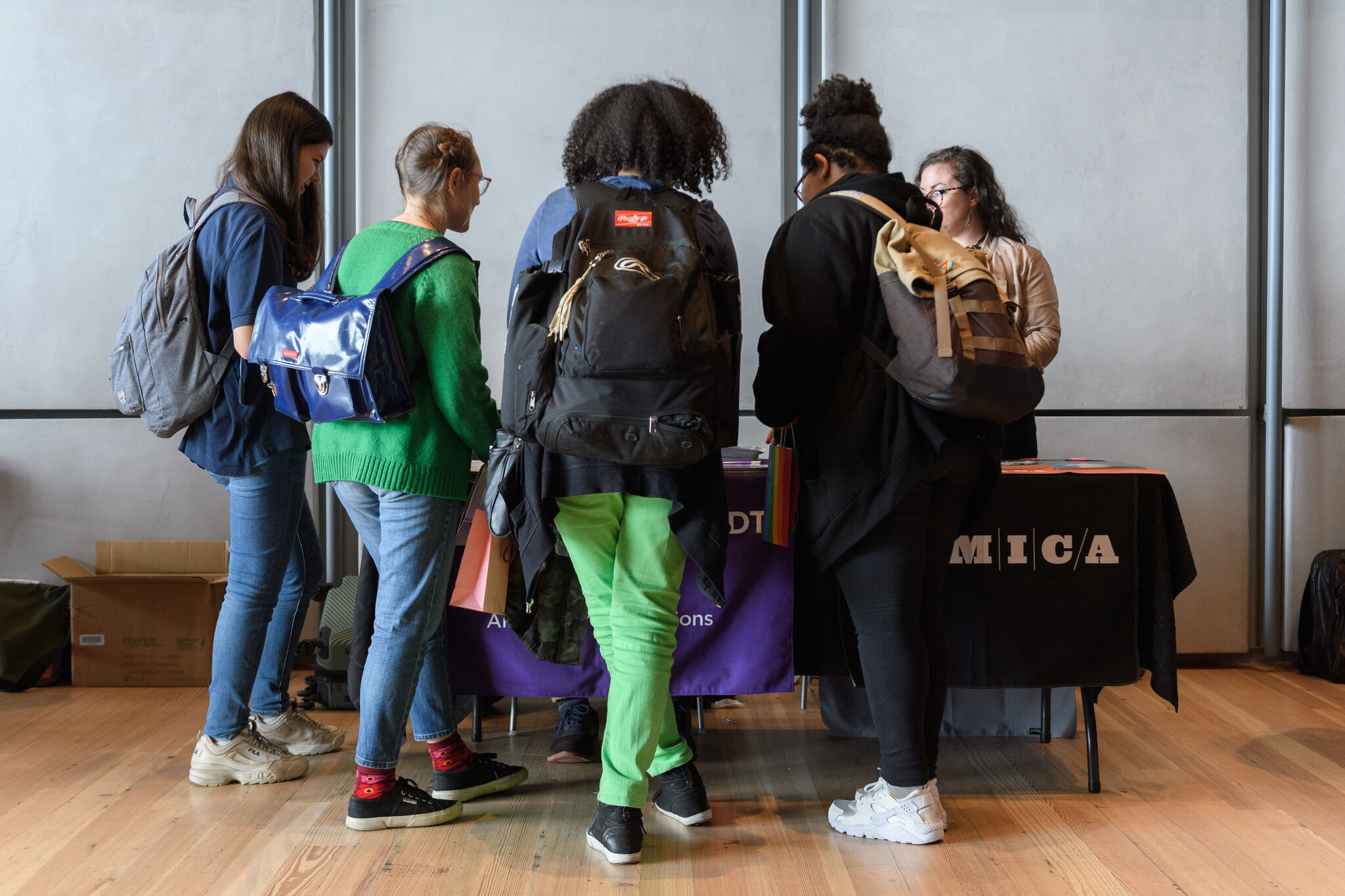A group of teenage people with backpacks on gather in front of information tables at the Whitney.