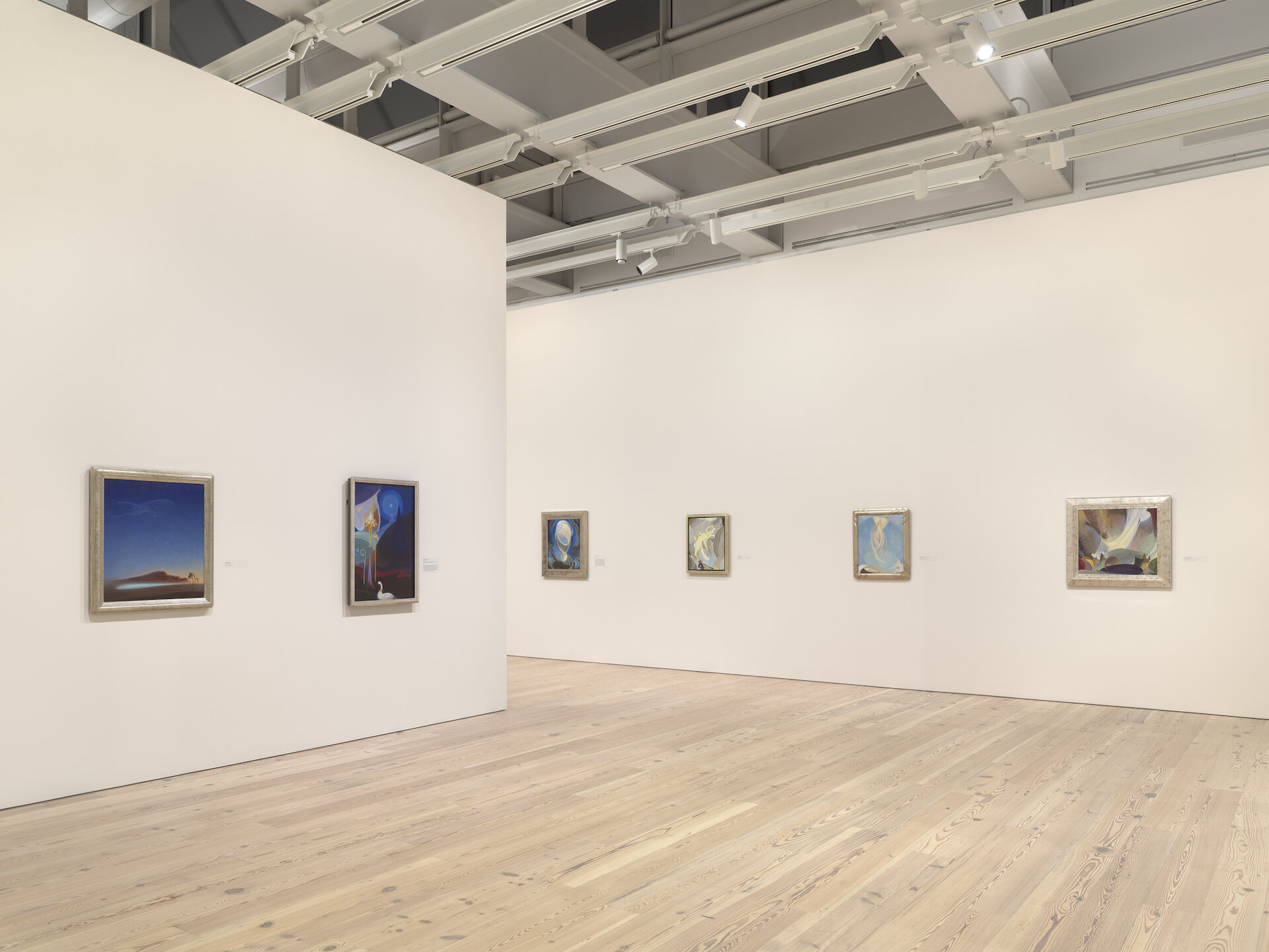 Paintings appear on white walls at the Whitney from the exhibition, Agnes Pelton: Desert Transcendentalist. The paintings that appear rrom left to right are: Return, 1940; Ahmi in Egypt, 1931; Being, 1926; Ecstasy, 1928; Meadowlark's Song, Winter, 1926; The Ray Serene, 1925.