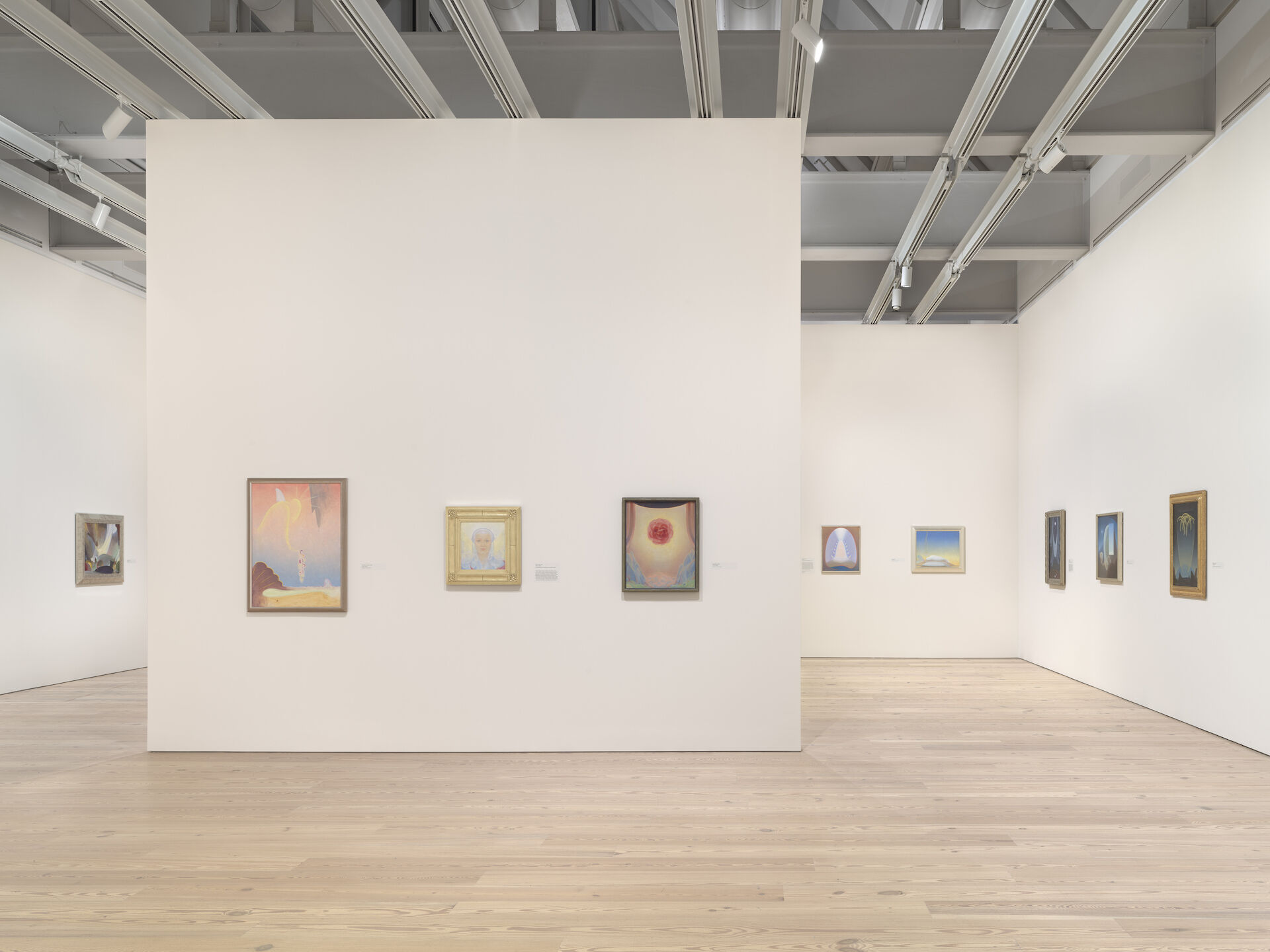 White exhibition walls appear at the end of a room at the Whitney. The walls contain paintings from Agnes Pelton: Desert Transcendentalist, including First Spring Garland, 1926; Barna Dilae, 1935; Incarnation, 1929; Mount of Flame, 1932, and more.