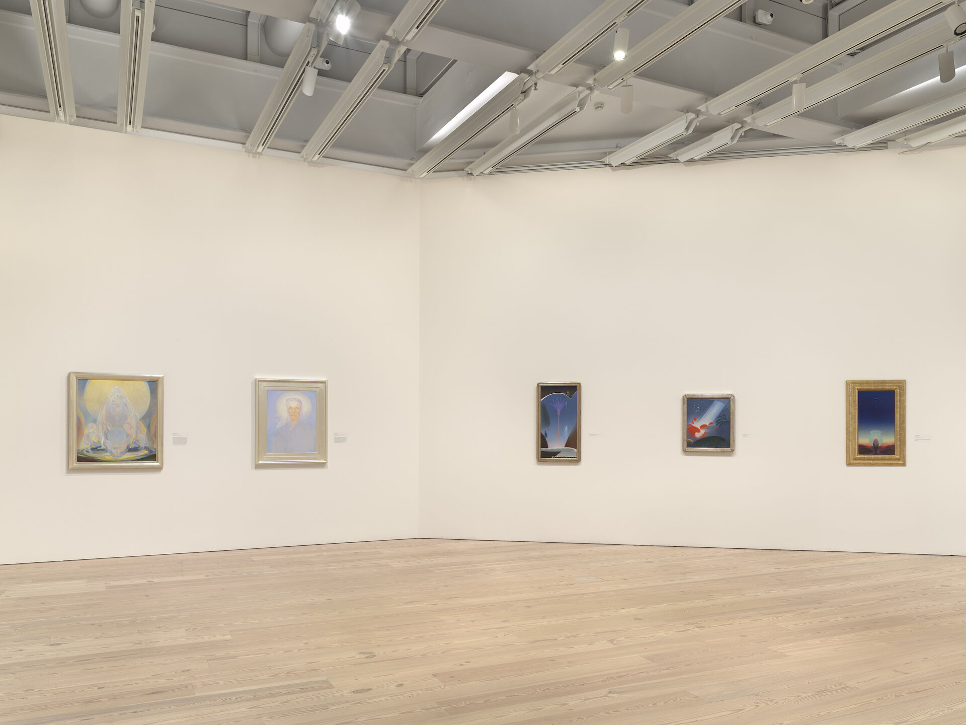 White walls meet at a corner in the middle of the image. Paintings by Agnes Pelton appear on the walls, from left to right: The Fountains, 1926; Intimation, 1933; Lotus for Lida (Egyptian Dawn), 1930; Red and Blue, c. 1938; Star Gazer, 1929.