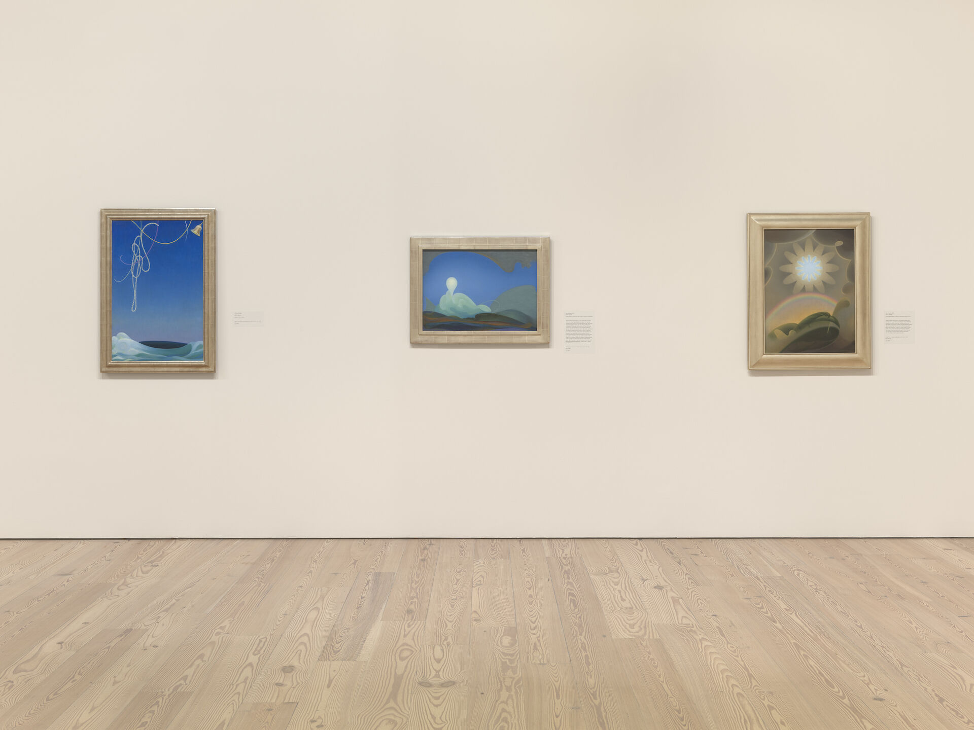 Three paintings by Agnes Pelton on a white wall. From left to right: Voyaging, 1931; Sea Change, 1931; Sand Storm, 1932.