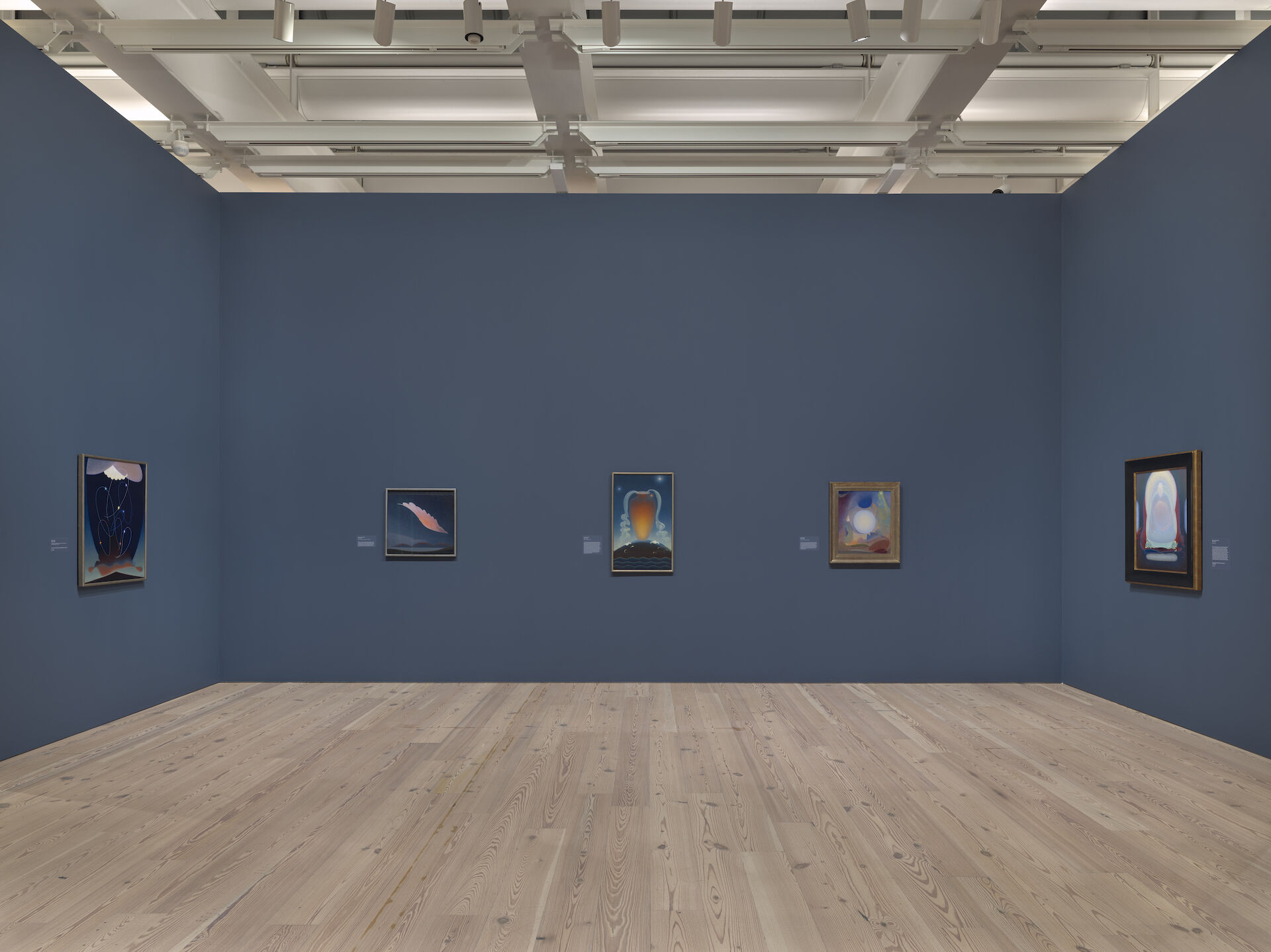 Looking into a blue room in the exhibition, Agnes Pelton: Desert Transcendentalist, paintings appear on the walls. From left to right: Orbits, 1934; The Primal Wing, 1933; Even Song, 1934; Interval, 1950; Mother of Silence, 1933.